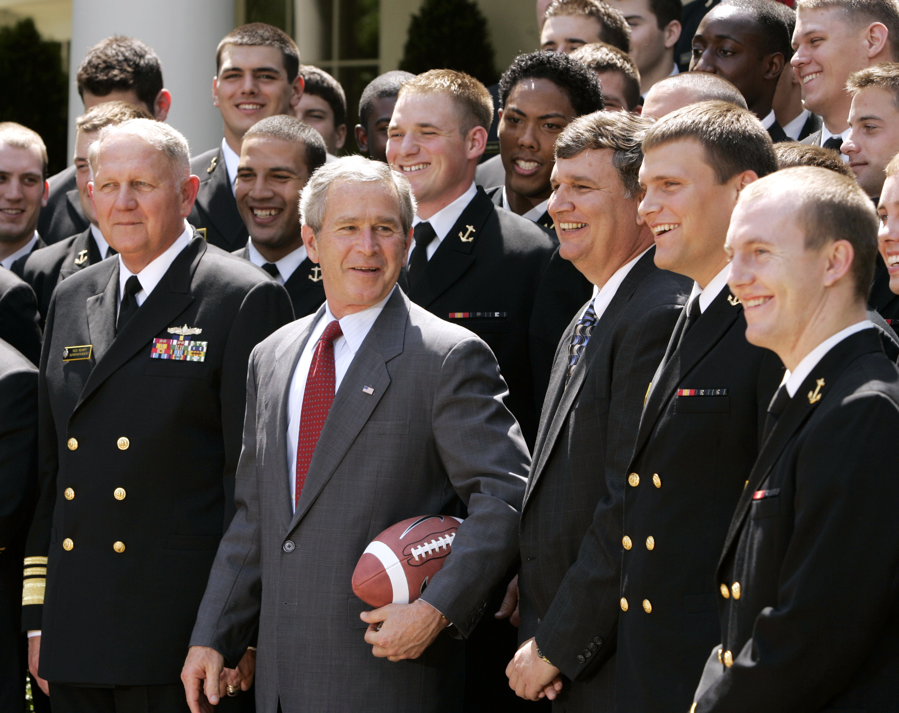 President Bush poses with members of the U.S. Naval Academy football team during a ceremony presenting the Commander in Chief trophy in the Rose Garden of the White House in Washington, Tuesday, April 25, 2006. Third from right is head coach Paul Johnson. (AP Photo/Gerald Herbert)