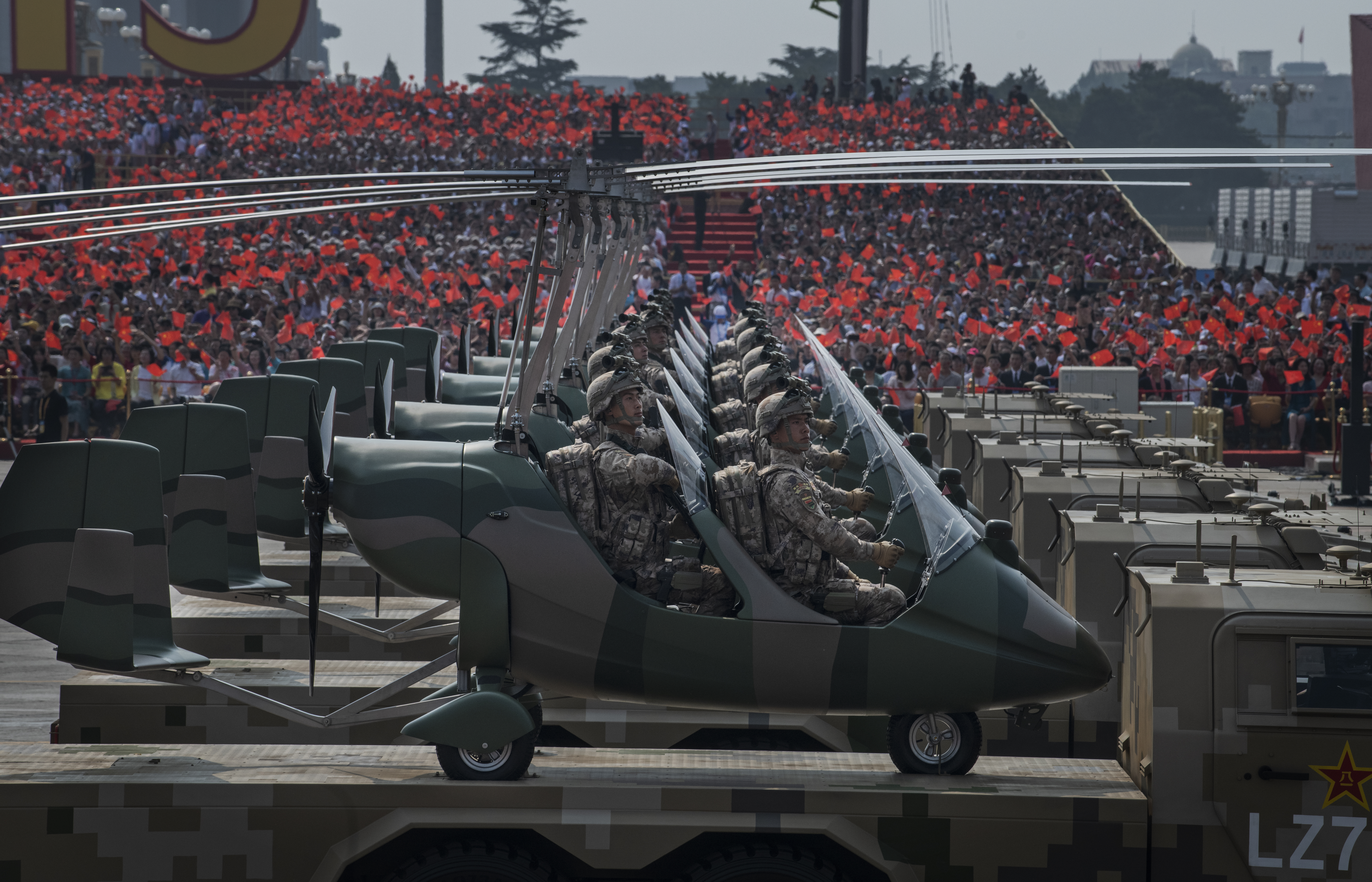 Chinese soldiers sit in small helicopters as they ride on trucks. (Kevin Frayer/Getty Images)