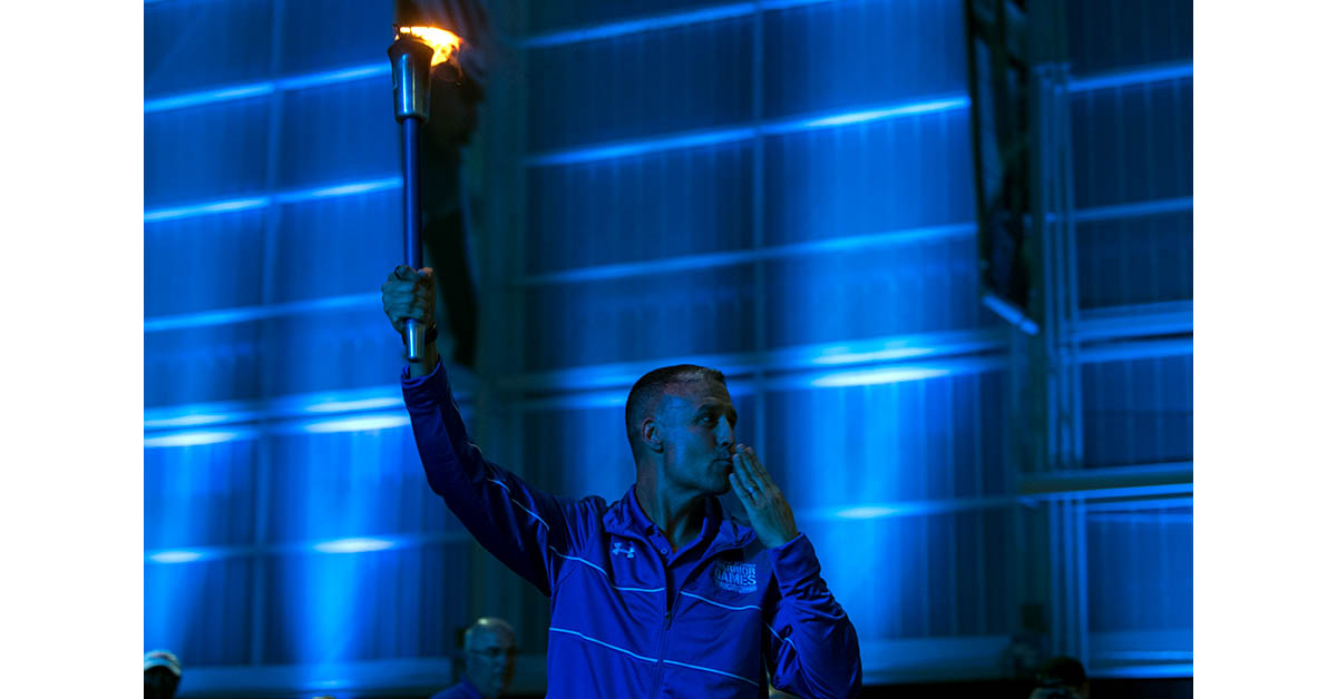 Retired Air Force Master Sgt. Shanon Hampton brings the DoD Warrior Games torch into the 2018 closing ceremony at the Air Force Academy in Colorado Springs, Colo. June 9, 2018. (EJ Hersom/DoD)