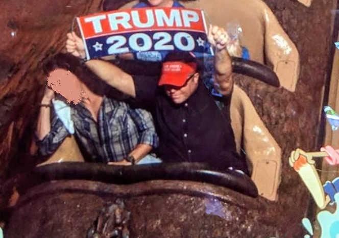 Dion Cini holds a Trump 2020 sign on Disney's Splash Mountain theme park ride. (Dion Cini Facebook)