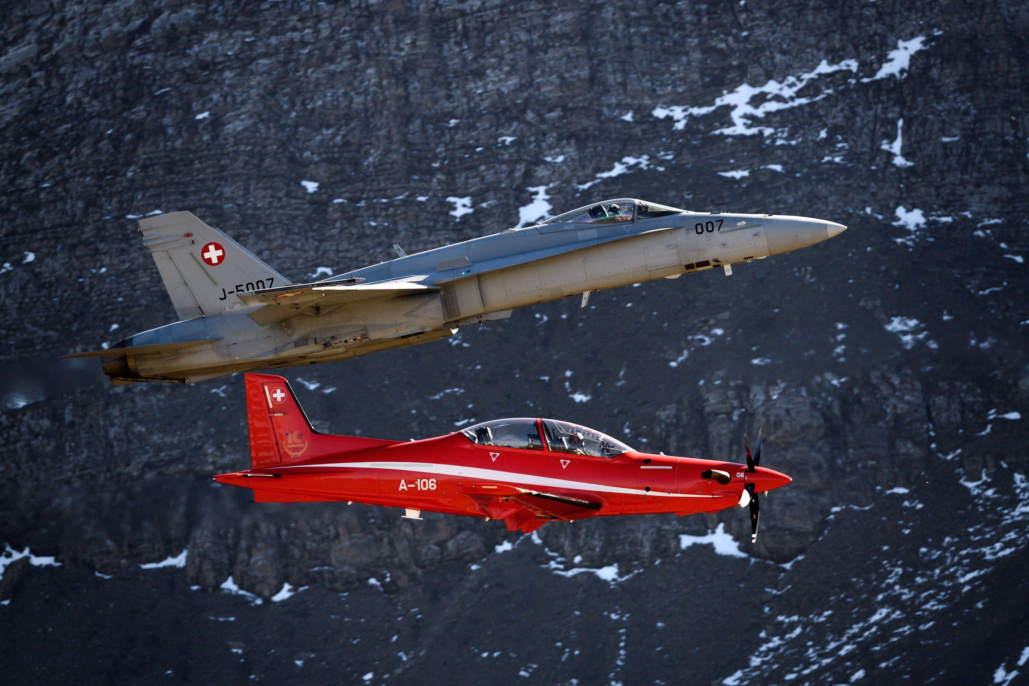 An F/A-18 Hornet fighter aircraft (above) flies next to a Pilatus PC-21 during the annual live fire event of the Swiss Air Force at the Axalp, over Brienz, in the Bernese Alps on Oct. 10, 2018. (Fabrice Coffrini/AFP/Getty Images)