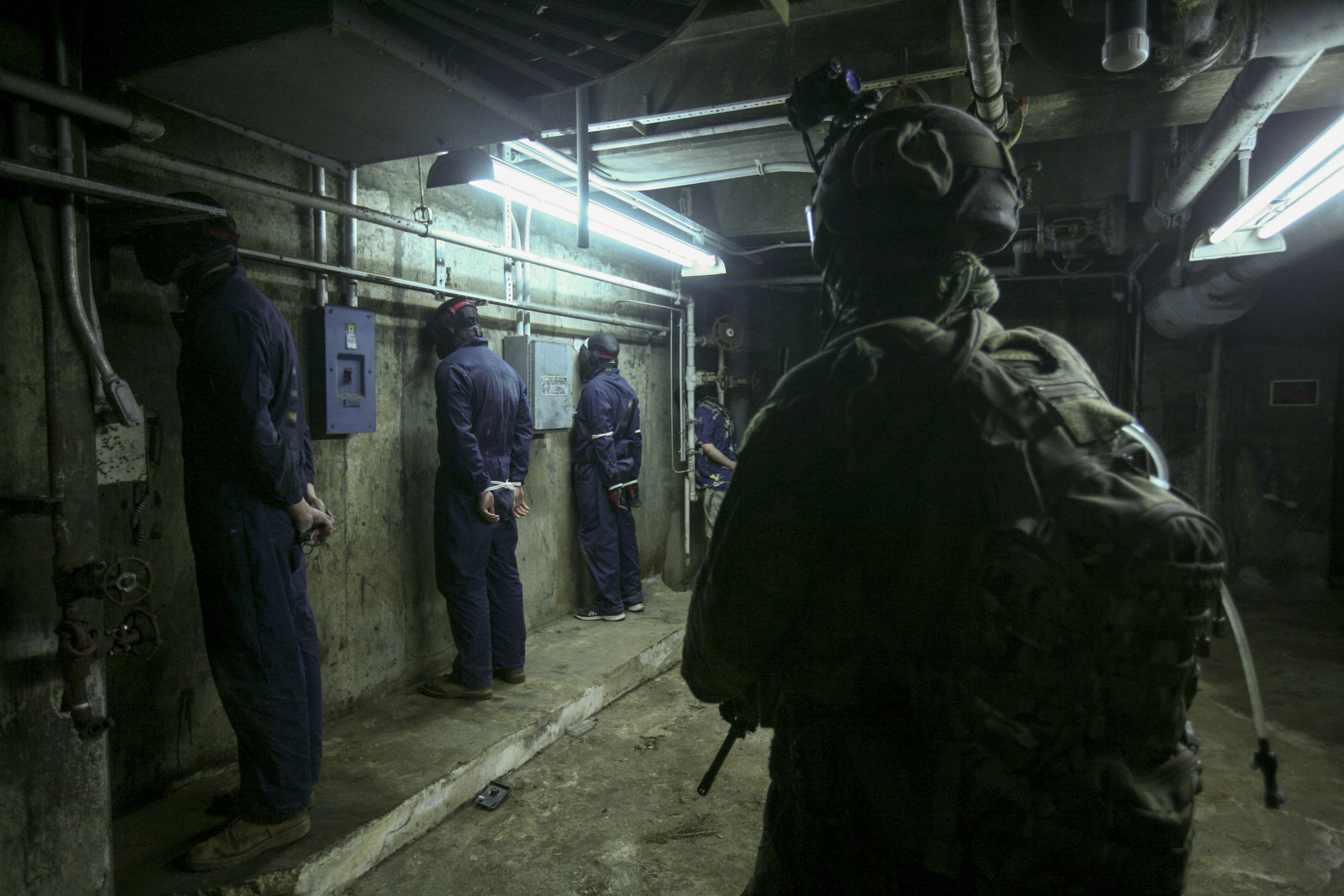 A Marine scout sniper holds security on four detainees during training. (Lance Cpl. Jorge A. Rosales/Marine Corps)