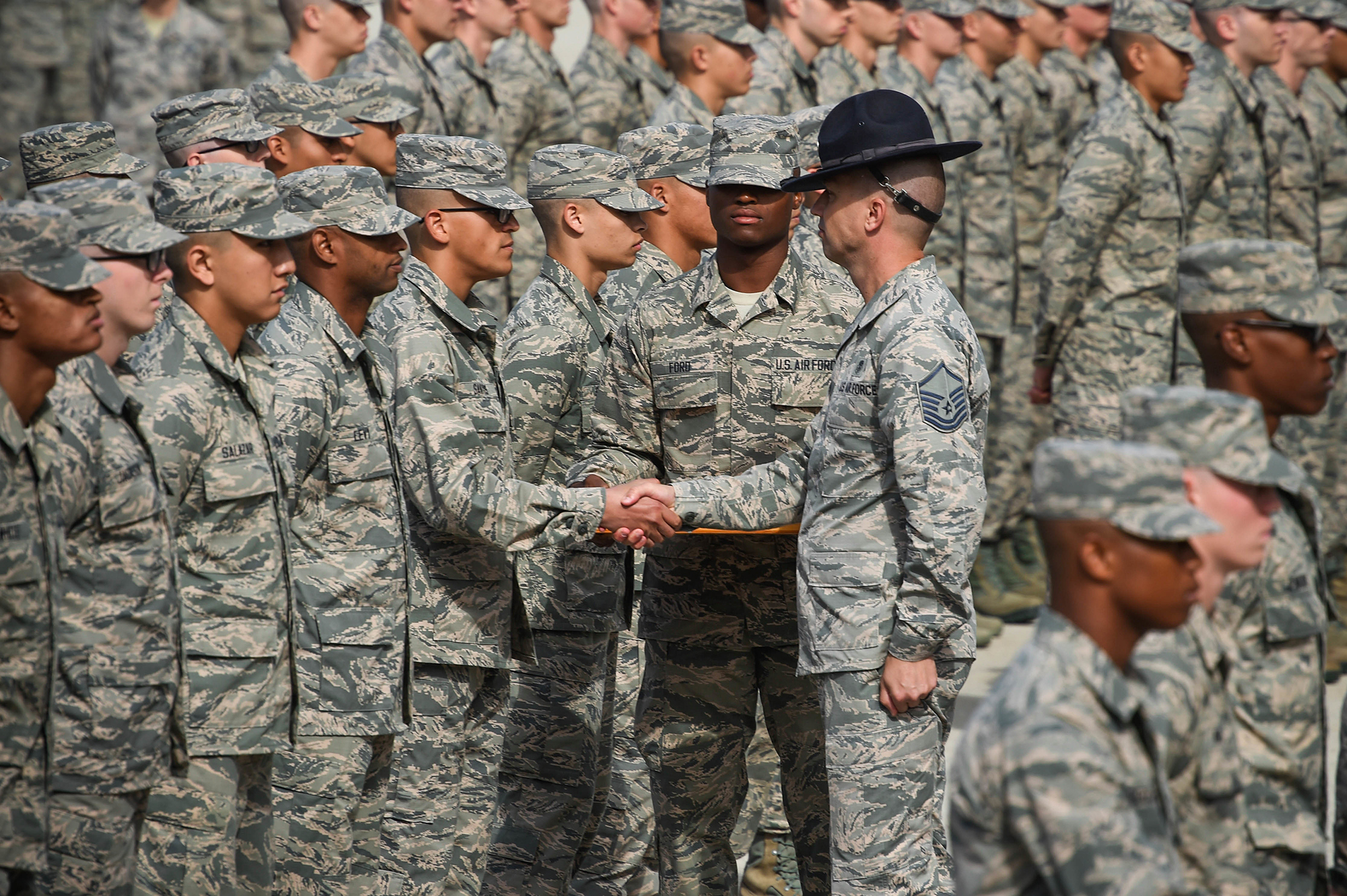 A military training instructor, center right, presents an airman's coin to one of his newly graduated trainees during the coin ceremony and retreat on Lackland Air Force Base, Texas, Oct. 17, 2019. The coin ceremony and retreat is the first time trainees are called airmen and the first day in eight weeks they are able to see their families and friends. (Airman 1st Class Mikayla Heineck/Air Force)