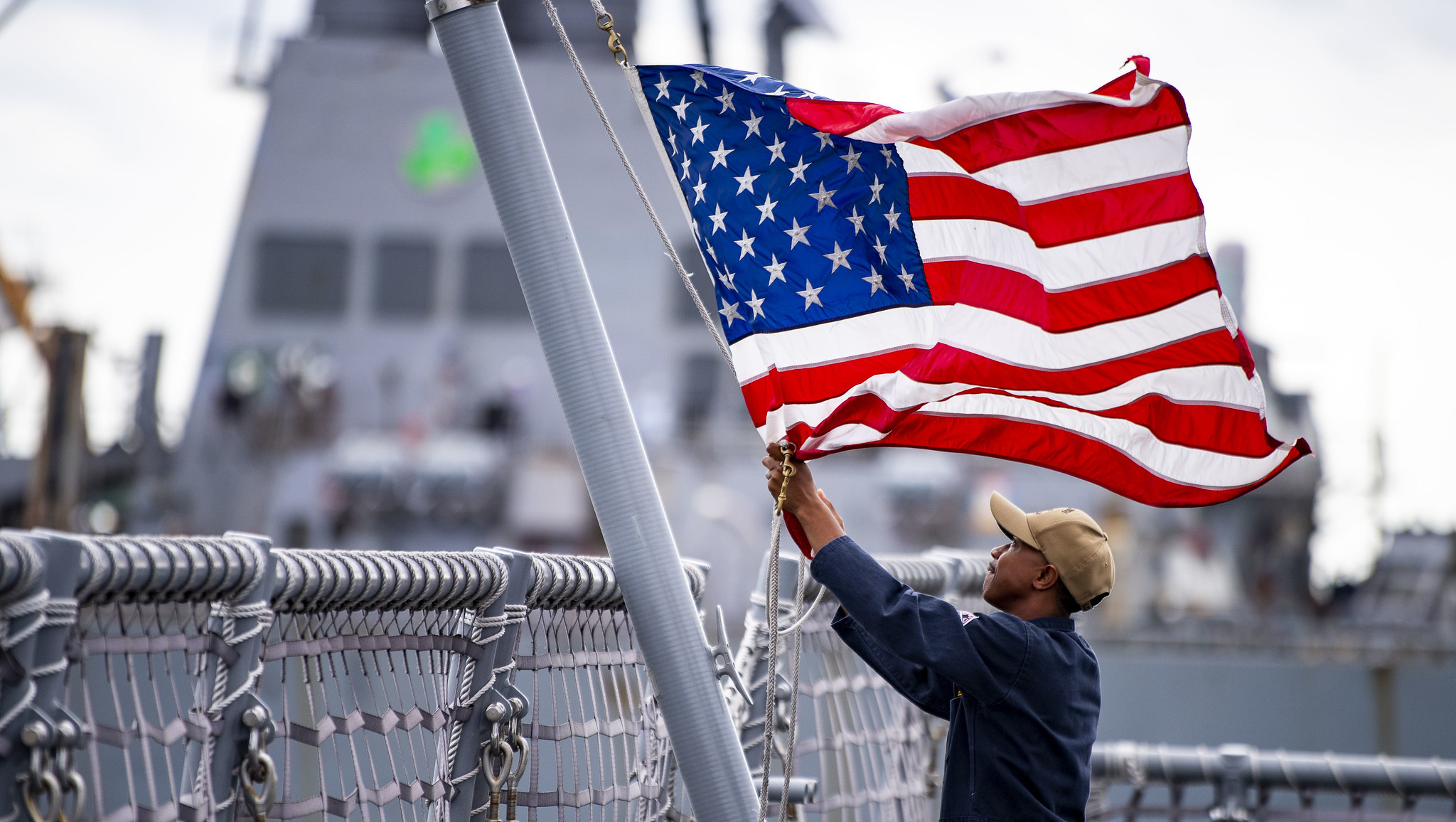 A sailor assigned to the Freedom-class variant littoral combat ship USS Billings (LCS 15) lowers the American flag Aug. 30, 2019, as the ship get underway from Naval Station Mayport. The commander of the U.S. 4th Fleet ordered all U.S. Navy ships homeported in the area to sortie ahead of Hurricane Dorian. (Mass Communication Specialist 3rd Class Nathan T. Beard/Navy)