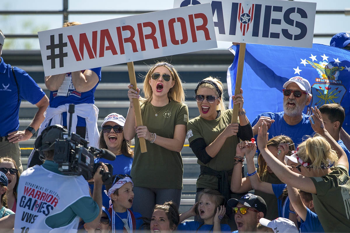 Fans cheer for their favorite athletes during a 2018 DoD Warrior Games Track Competition at the U.S. Air Force Academy in Colorado Springs, Colorado, June 2, 2018. The Warrior Games is an adaptive sports competition for wounded, ill and injured service members and veterans. Approximately 300 athletes representing teams from the Marine Corps, Navy, Army, Air Force, Special Operations Command, United Kingdom Armed Forces, Canadian Armed Forces, and the Australian Defence Force will compete June 1 - June 9 in archery, cycling, track, field, shooting, sitting volleyball, swimming, wheelchair basketball, and - new this year - powerlifting and indoor rowing. (Cpl. Julien Rodarte/Marines)