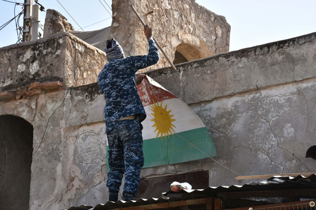 An Iraqi fighter loyal to the federal government attempts to remove a sheet metal sign painted with the colors of the Kurdish flag from a building in the region of Altun Kupri, about 50 kilometres (30 miles) from Arbil, capital of autonomous Iraqi Kurdistan, on Oct. 20, 2017. (Marwan Ibrahim/AFP/Getty Images)