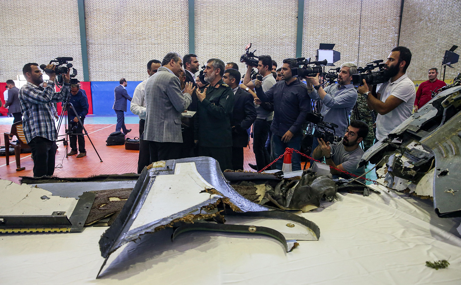 Gen. Amir Ali Hajizadeh, center, Iran's head of the Revolutionary Guard's aerospace division, speaks to media next to debris from a downed U.S. drone reportedly recovered within Iran's territorial waters and put on display by the Revolutionary Guard in the capital Tehran on June 21, 2019. (Meghdad Madadi/AFP/Getty Images)