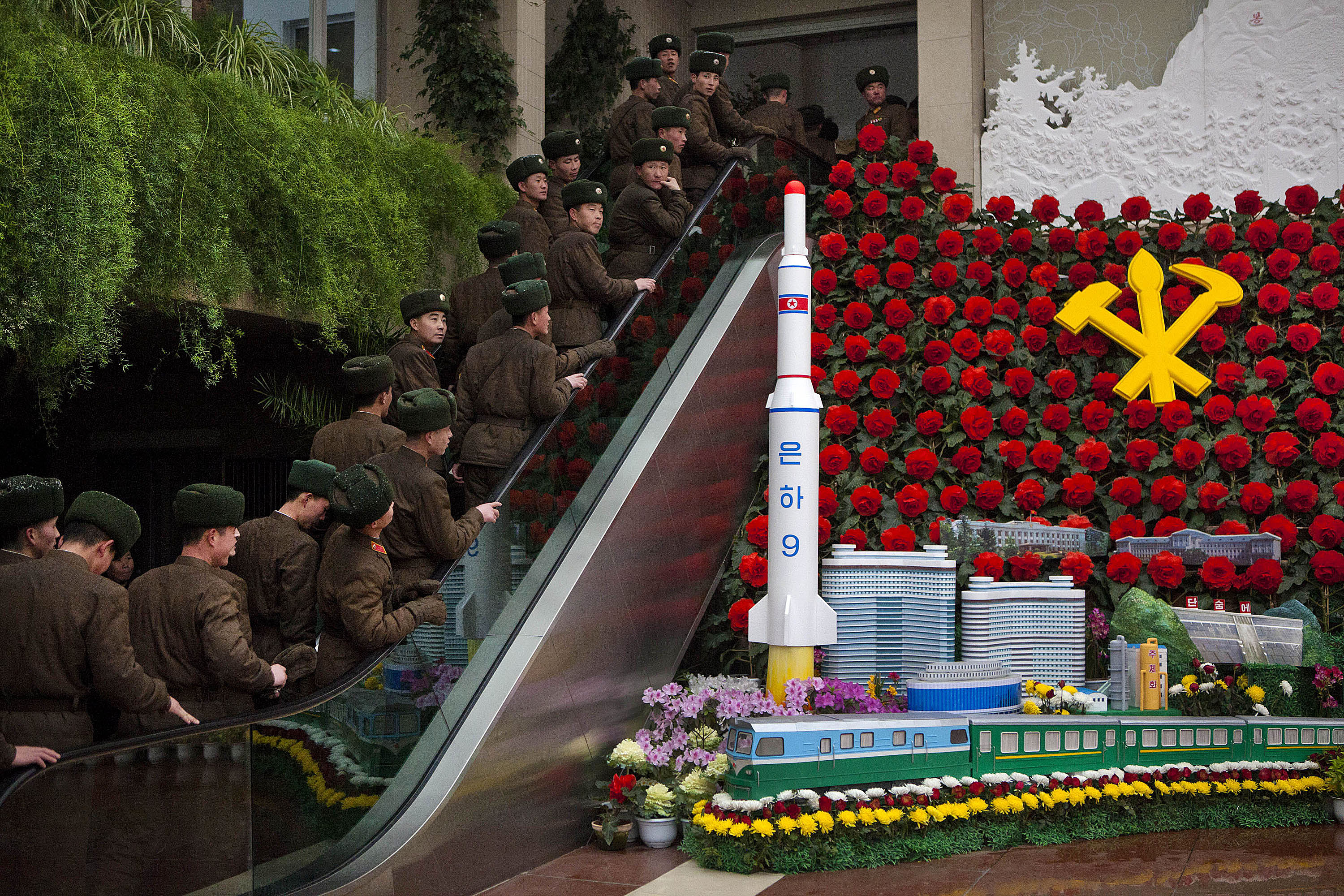 North Korean soldiers ride an escalator past a model of their country's Unha Rocket as they enter an exhibition in Pyongyang on Feb. 17, 2013. (David Guttenfelder/AP)