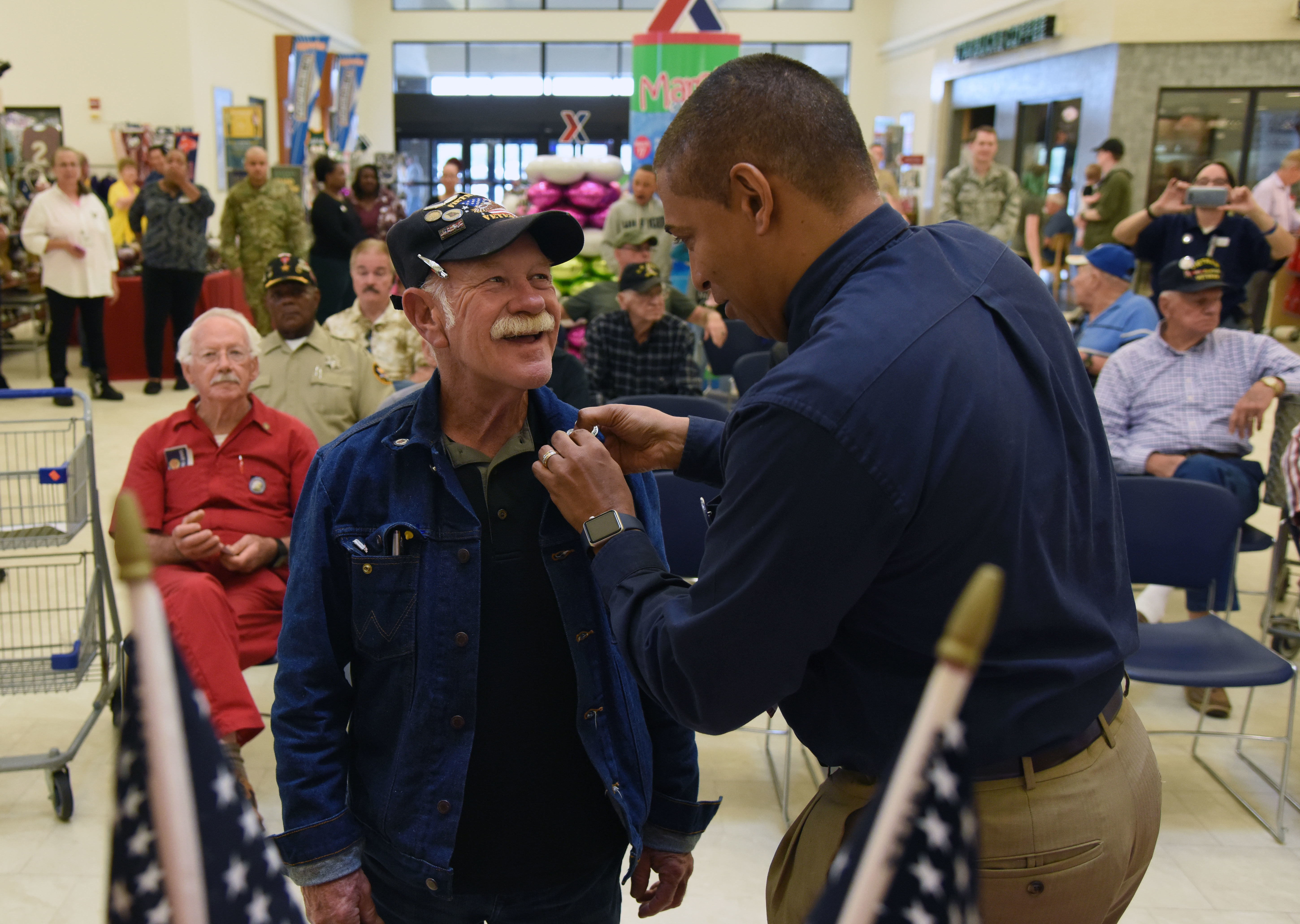 Gregory Hall, Keesler Base Exchange general manager, presents a lapel pin to Roger Anderson, U.S. Navy Vietnam veteran, during the 50th Anniversary Vietnam Memorial Pinning Day at The Exchange March 29, 2018, on Keesler Air Force Base, Mississippi. The event, which also included a cake cutting ceremony, was held to honor Vietnam veterans for their service. (Kemberly Groue/Air Force)