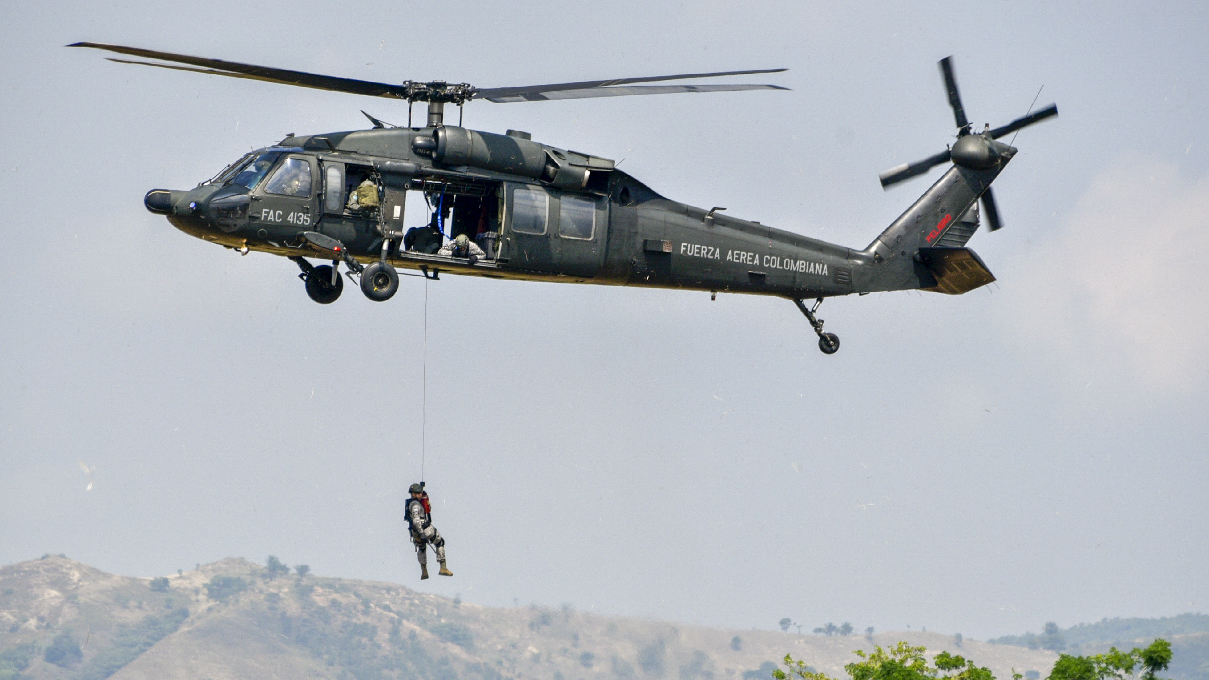 A soldier rappels from a helicopter during a demonstration by the military forces at President Ivan Duque's launch of the new national security and defense policy at the Tolemaida military fort in Cundinamarca, Colombia, on February 6, 2019. (GUILLERMO LEGARIA/AFP/Getty Images)