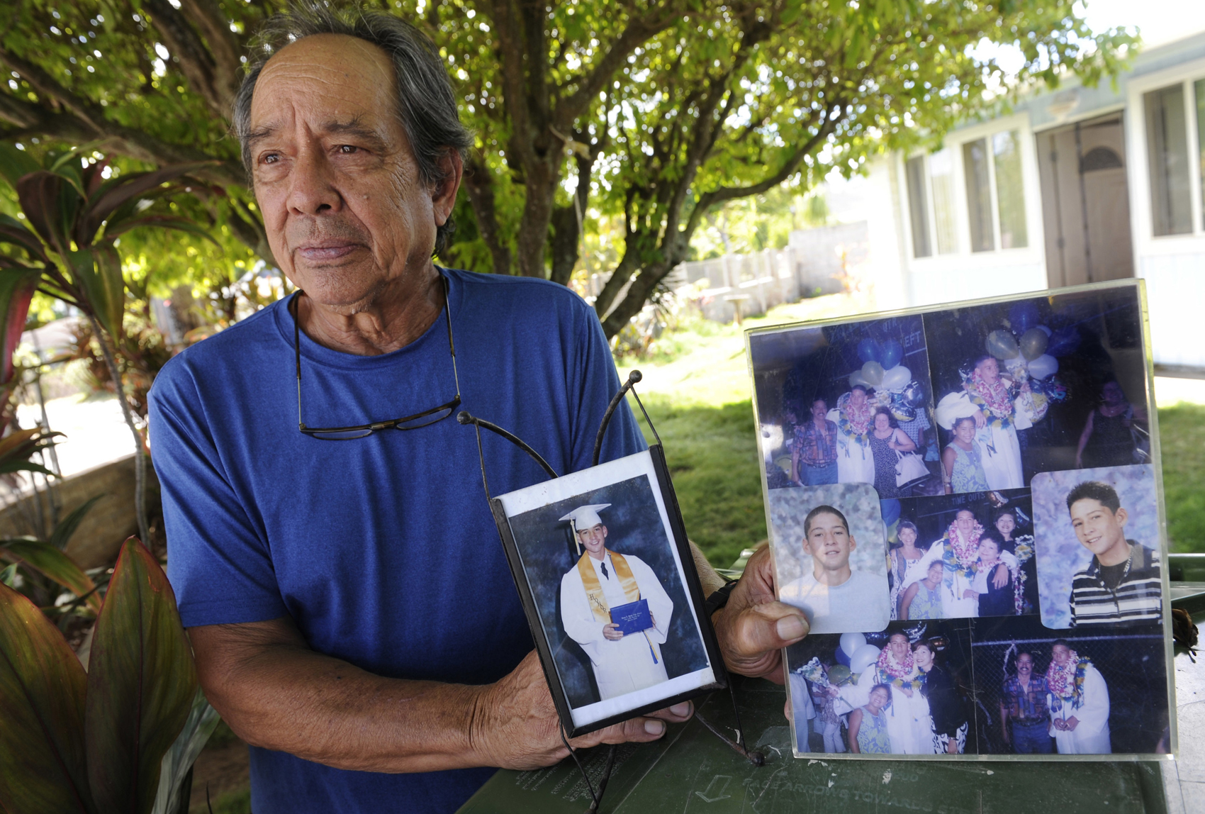 In this July 10, 2017, photo, Clifford Kang, father of soldier Ikaika E. Kang, poses with photos of his son in Kailua, Hawaii. (Bruce Asato/The Star-Advertiser via AP)