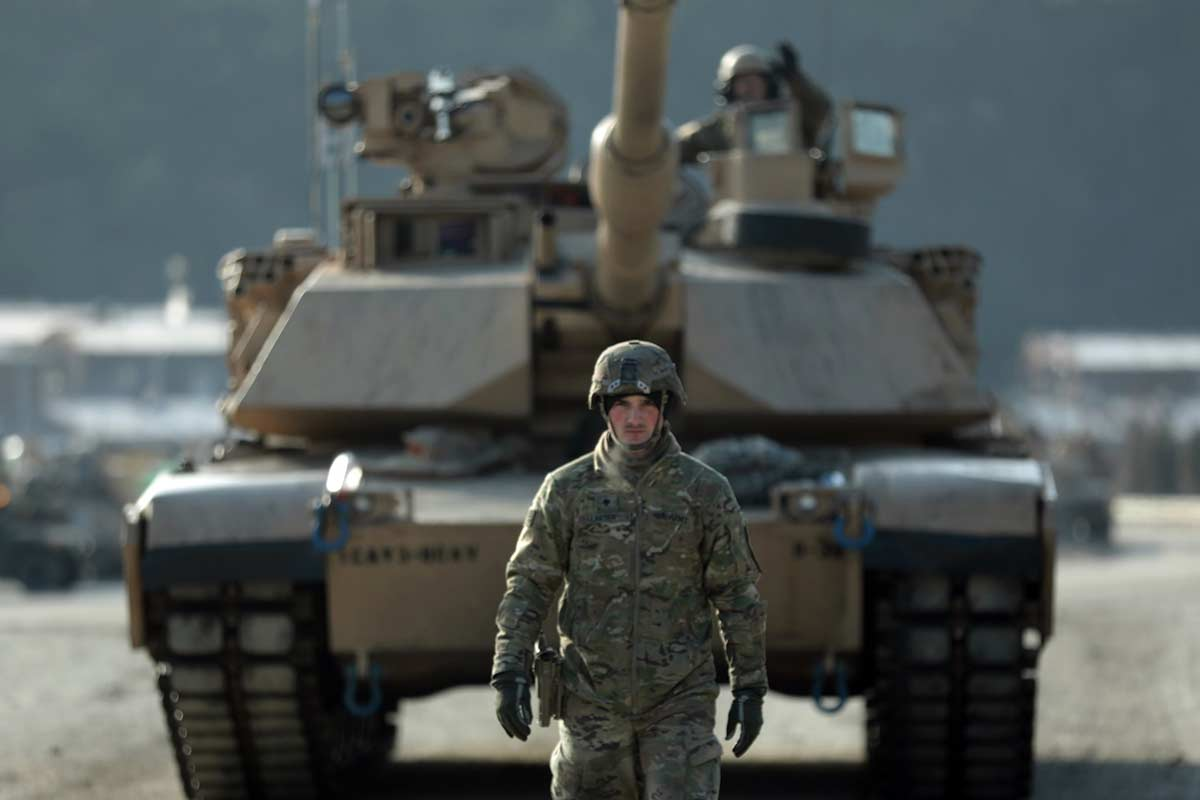A tank crewman with 3rd Battalion, 8th Cavalry Regiment, 3rd Armored Brigade Combat Team, 1st Cavalry Division, ground guides his tank in the Republic of Korea, Nov. 19, 2019, during the battalion's gunnery qualifications. (Capt. Scott Kuhn/Army)