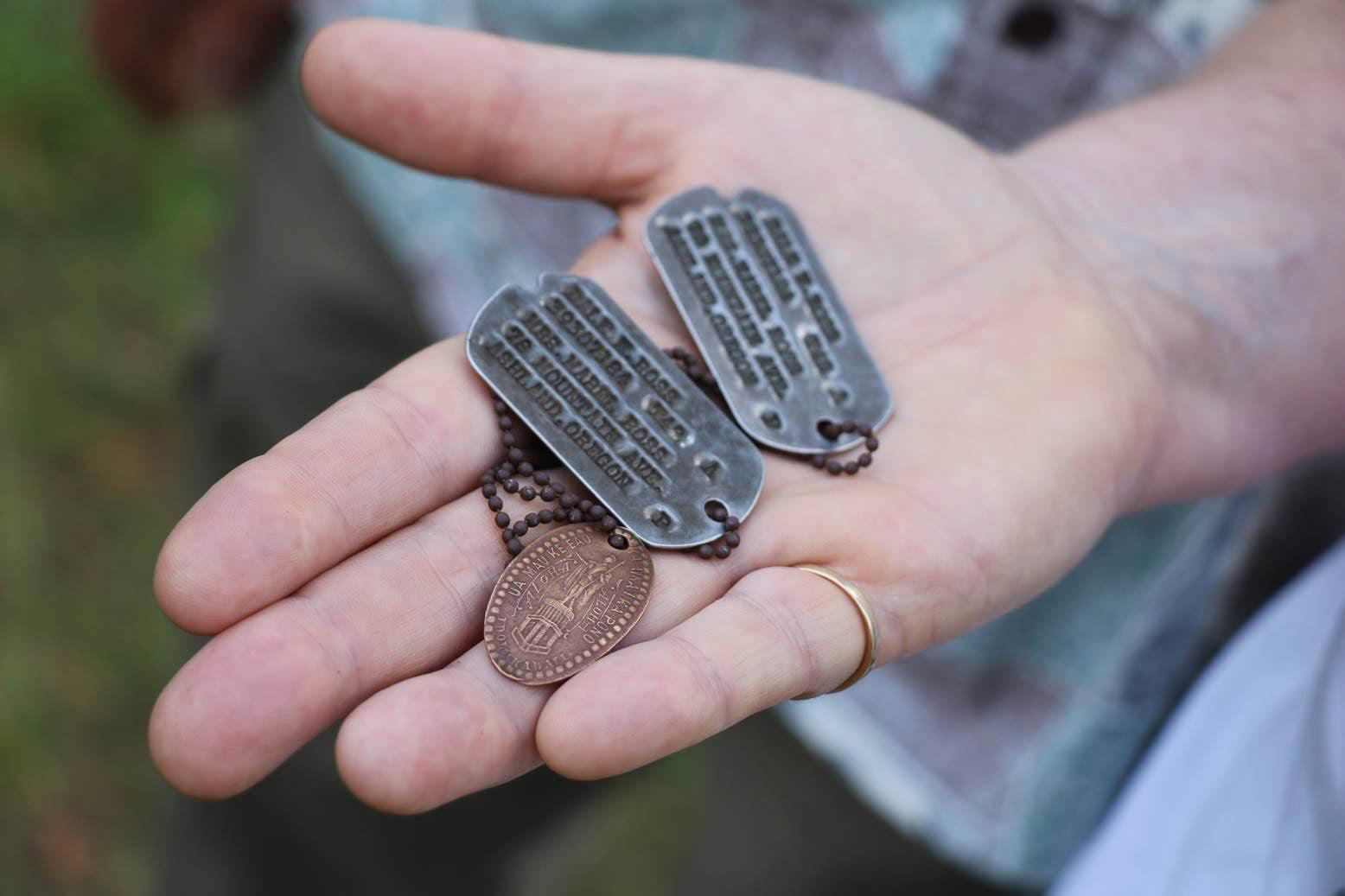 In this Aug. 3, 2017, photo, the dog tags and a Hawaiian pressed penny charm of Pfc. Dale W. Ross are displayed at Guadalcanal in the Solomon Islands. (Justin Taylan/Pacific Wrecks via AP)