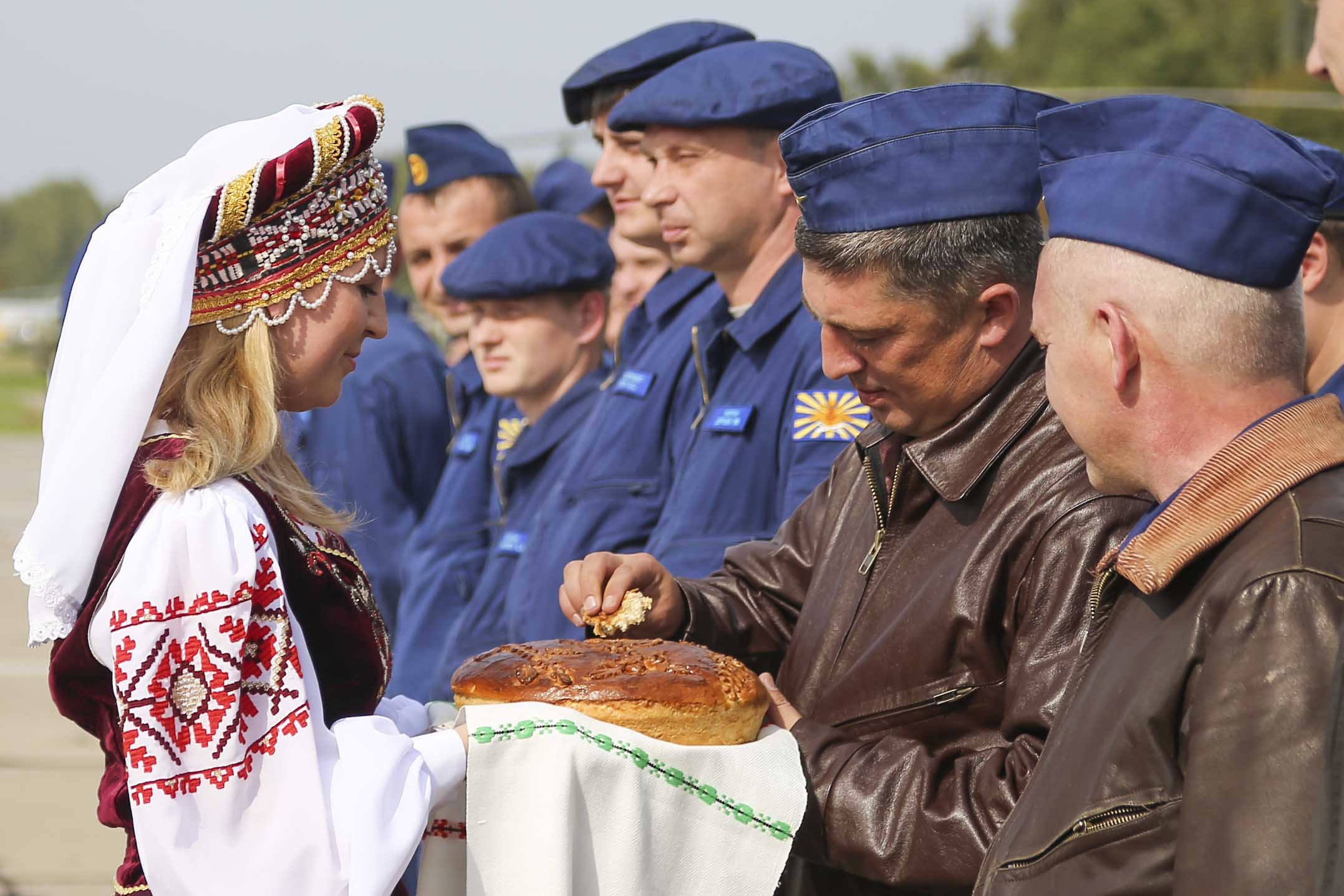 Russian military pilots are presented with bread and salt as they arrive at an air base at an undisclosed location in Belarus on Sept. 12, 2017. Russia and Belarus are holding a massive war game, Zapad 2017, which states Sept. 14, 2017, near the borders of Poland, Estonia, Latvia and Lithuania. (Vayar Military Agency photo via AP)