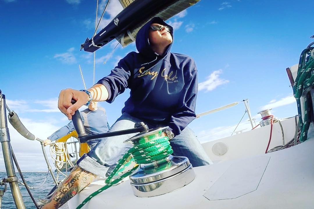 Brian Bugge works the winch aboard the Stay Gold on a windy day on the Puget Sound. Now an ensign, Bugge previously served as a chief petty officer. (Courtesy of Ashley Bugge)