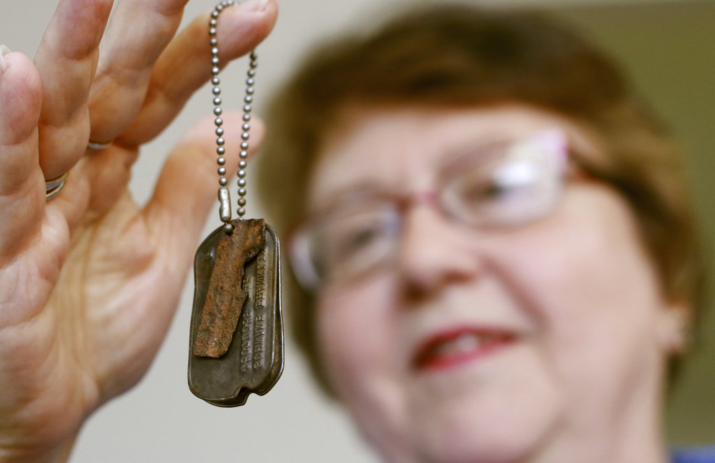 In this July 10, 2018, photo, Mary Beth Seiser holds her father's dog tags at her home in West Bend, Wis. (John R. Ehlke/West Bend Daily News via AP)
