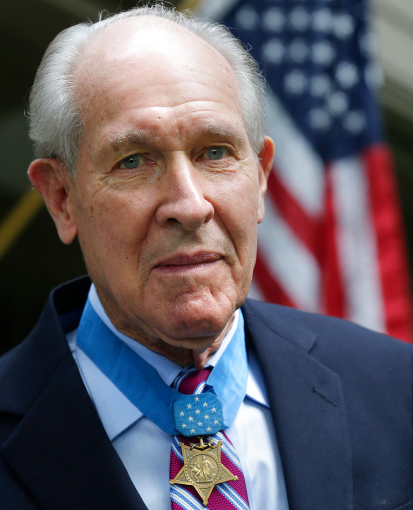 In this July 12, 2013, file photo, retired U.S. Navy Capt. Thomas Hudner, who was awarded the Medal of Honor by President Truman, poses on the porch at his home in Concord, Mass. Hudner intentionally crashed his plane during the Korean War in 1950 to try to save his wingman Jesse Brown, whose plane had been shot down. Hudner died Monday, Nov. 13, 2017, at age 93, and will be buried Wednesday, April 4, 2018, at Arlington National Cemetery in Arlington, Va. (Charles Krupa/AP)