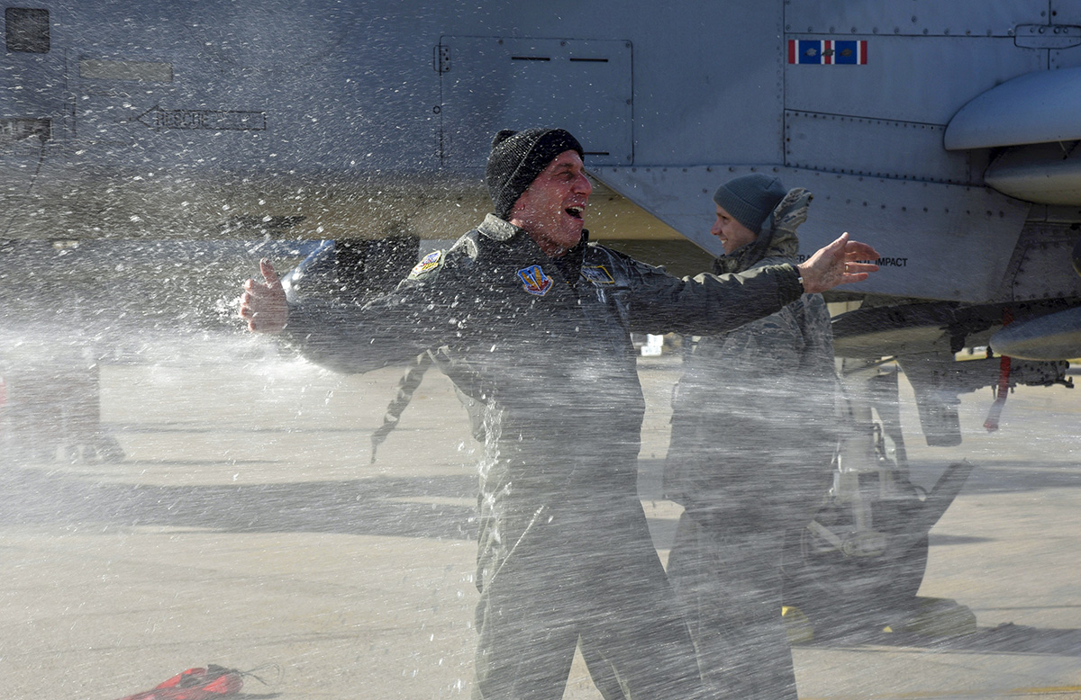 Air Force Col. Paul Zurkowski, a pilot assigned to the 104th Fighter Squadron, is sprayed by family members March 3rd, 2018, after his fini flight at Warfield Air National Guard Base, Middle River, Md. Spraying pilots with fire hoses and champagne is part of a tradition that celebrates a pilot's fini flight, or final flight, with their unit or on a certain aircraft. (A1C Sarah M. McClanahan/Air Force)