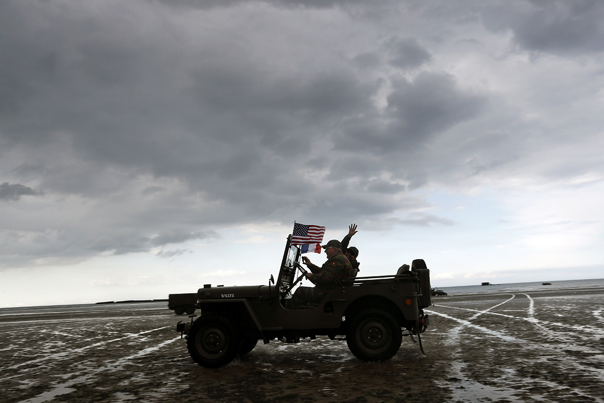 Enthusiasts ride a jeep on the beach of Arromanches, Tuesday, June 4, 2019, in Normandy. Extensive commemorations are being held in the U.K. and France this week to honor the nearly 160,000 troops from Britain, the United States, Canada and other nations who landed in Normandy on June 6, 1944, in history's biggest amphibious invasion. (Thibault Camus/AP)