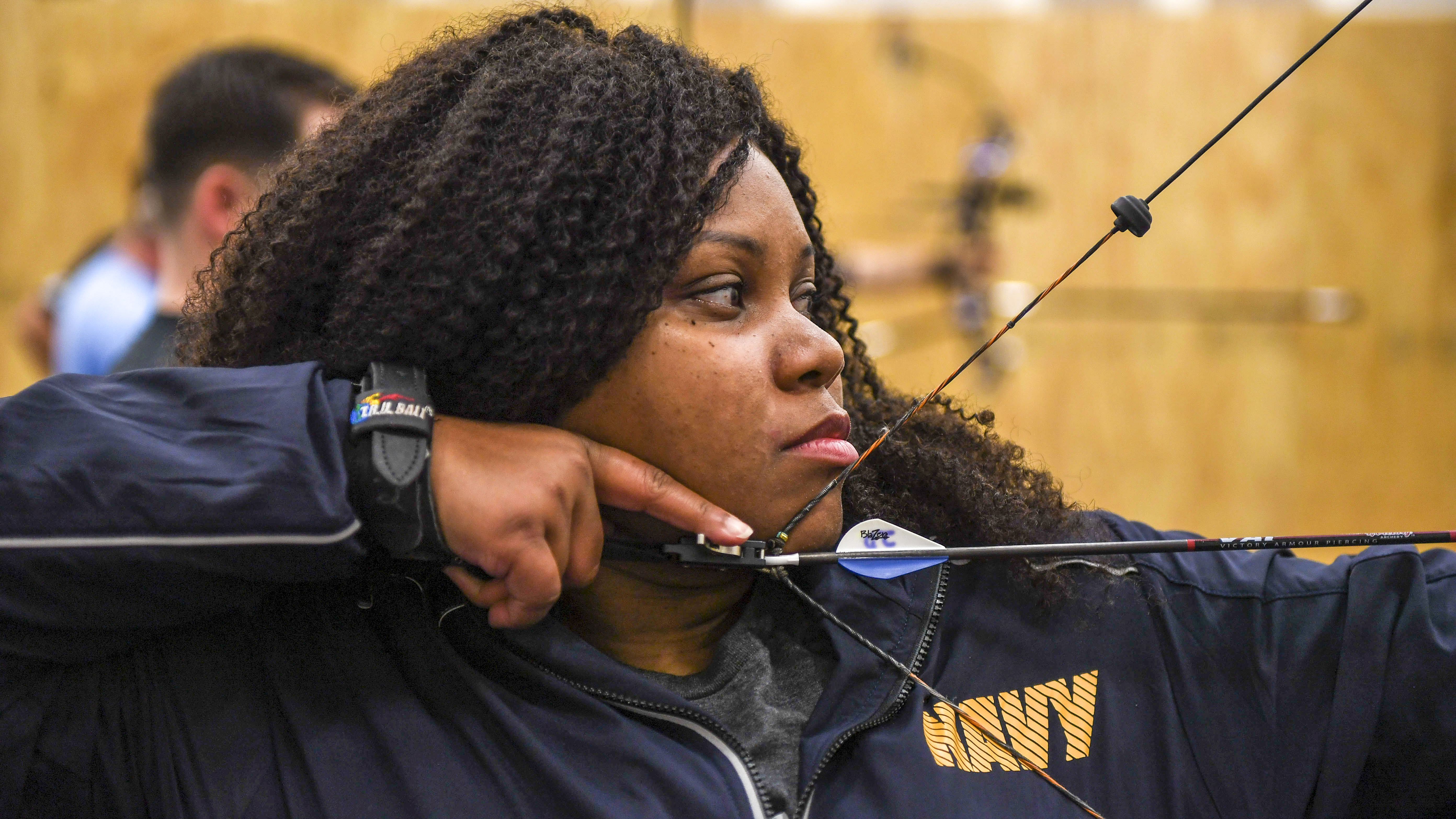 Yeoman 3rd Class Alexis King shoots a bow during archery training prior to the Team Navy trials at Naval Station Mayport's fitness center in preparation for the 2018 Department of Defense Warrior games. Navy Wounded Warrior-Safe Harbor and NAVSTA Mayport are hosting the trials, in which athletes will qualify in eight adaptive sports: archery, track and field, cycling, wheelchair basketball, shooting, sitting volleyball, and swimming. The top performing athletes will fill 40 competitive spots and five alternative spots for Team Navy at the 2018 Department of Defense Warrior Games. (MC2 Michael Lopez/Navy)