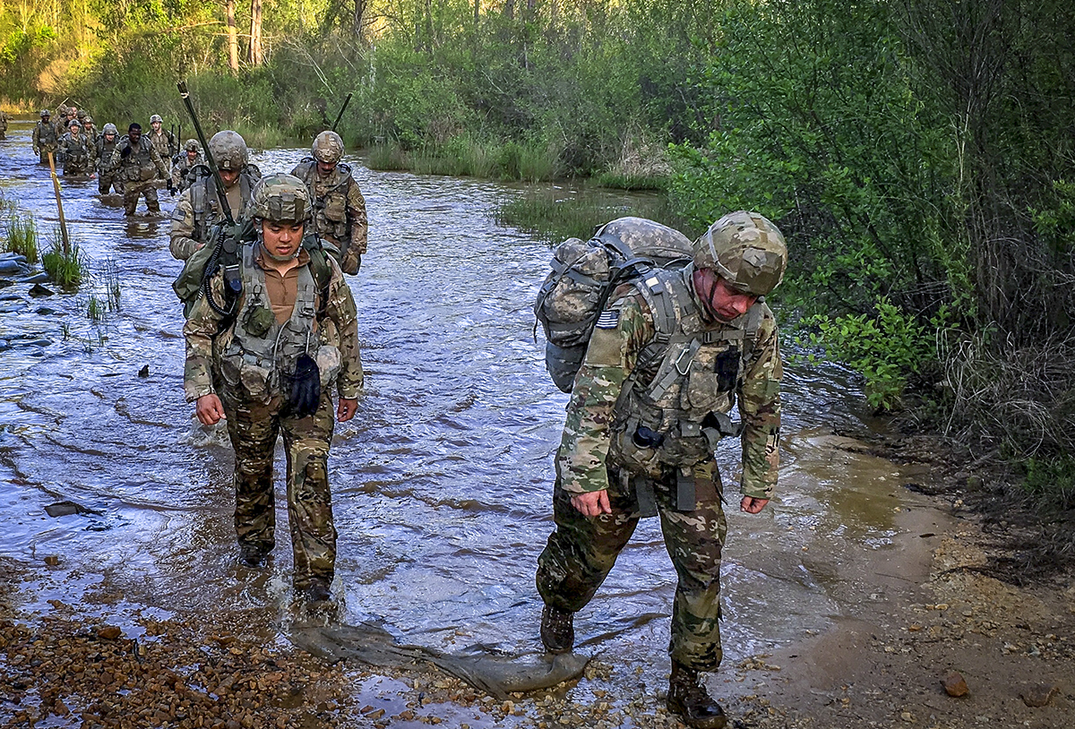 Paratroopers assigned to Headquarters, Headquarters Company, 3rd Brigade Combat Team, 82nd Airborne Division wade through a river while conducting a ruck march. The ruck march was part of the company's assault command post physical training and helped the paratroopers train for future operations while building teamwork. (Maj. Thomas Cieslak/Army)