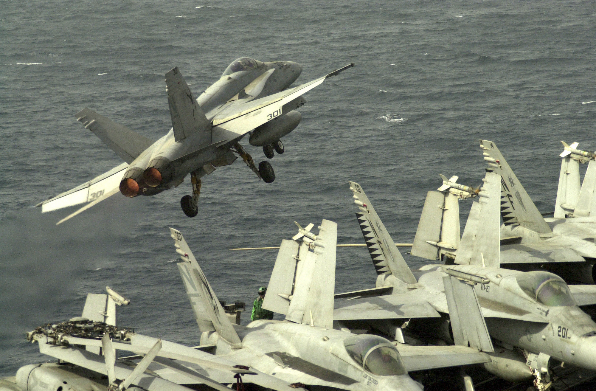 ABOARD THE USS KITTY HAWK - MARCH 20, 2003 - Loaded with missiles and bombs, an F/A-18 Hornet from Strike Fighter Squadron 192 catapults off the aircraft carrier Kitty Hawk during an early afternoon launch. Eight Hornets, including some from VFA-192 and two F-14 Tomcats from Fighter Squadron 154, flying off the Kitty Hawk hit targets in southeastern Iraq March 19 in response to Iraqi provocation. Still flying under