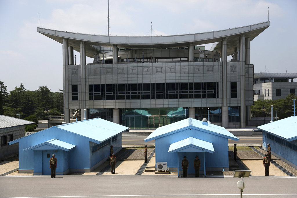 The South Korean buildings are seen in the background as North Korean soldiers stand guard at the truce village at the Demilitarized Zone (DMZ) which separates the two Koreas in Panmunjom, North Korea, Wednesday, June 20, 2018. (Dita Alangkara/AP)