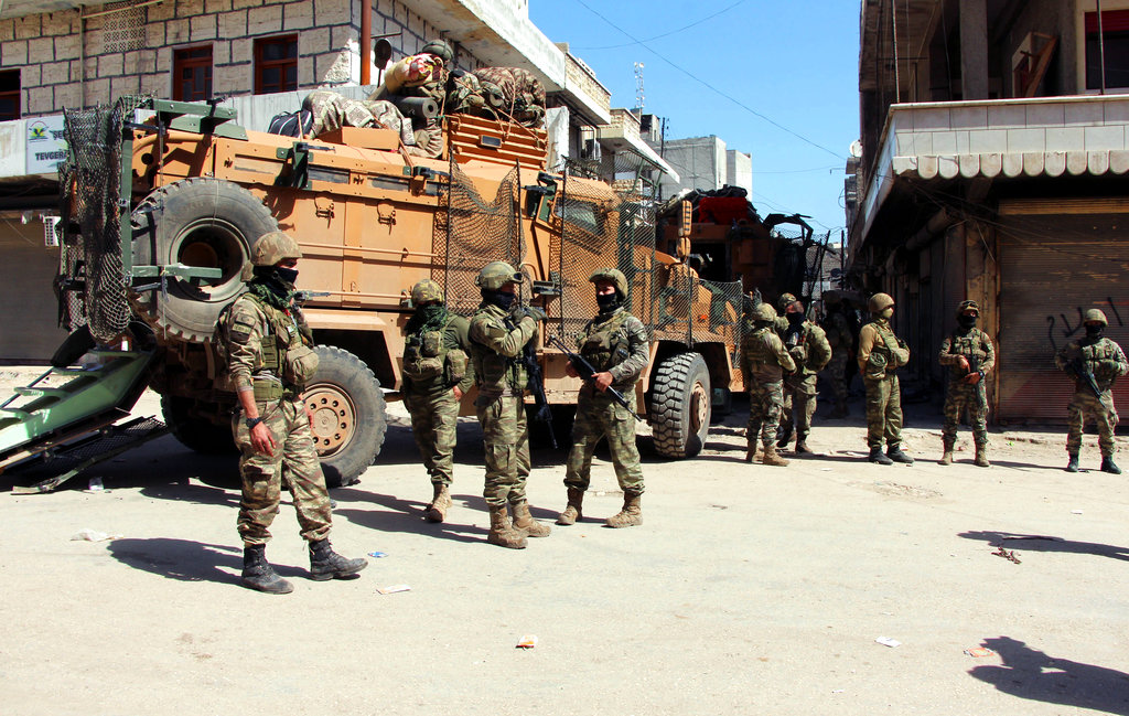 Turkish soldiers, positioned in the city center of Afrin, northwestern Syria, Monday, March 19, 2018, a day after they took the control of the area. Turkey's President Recep Tayyip Erdogan said Monday following victory in Syria's Afrin region, his country will expand its military operations into other Kurdish-held areas in Syria as well as in Iraq's Sinjar region. (Hasan Kırmızitaş/DHA-Depo Photos via AP)