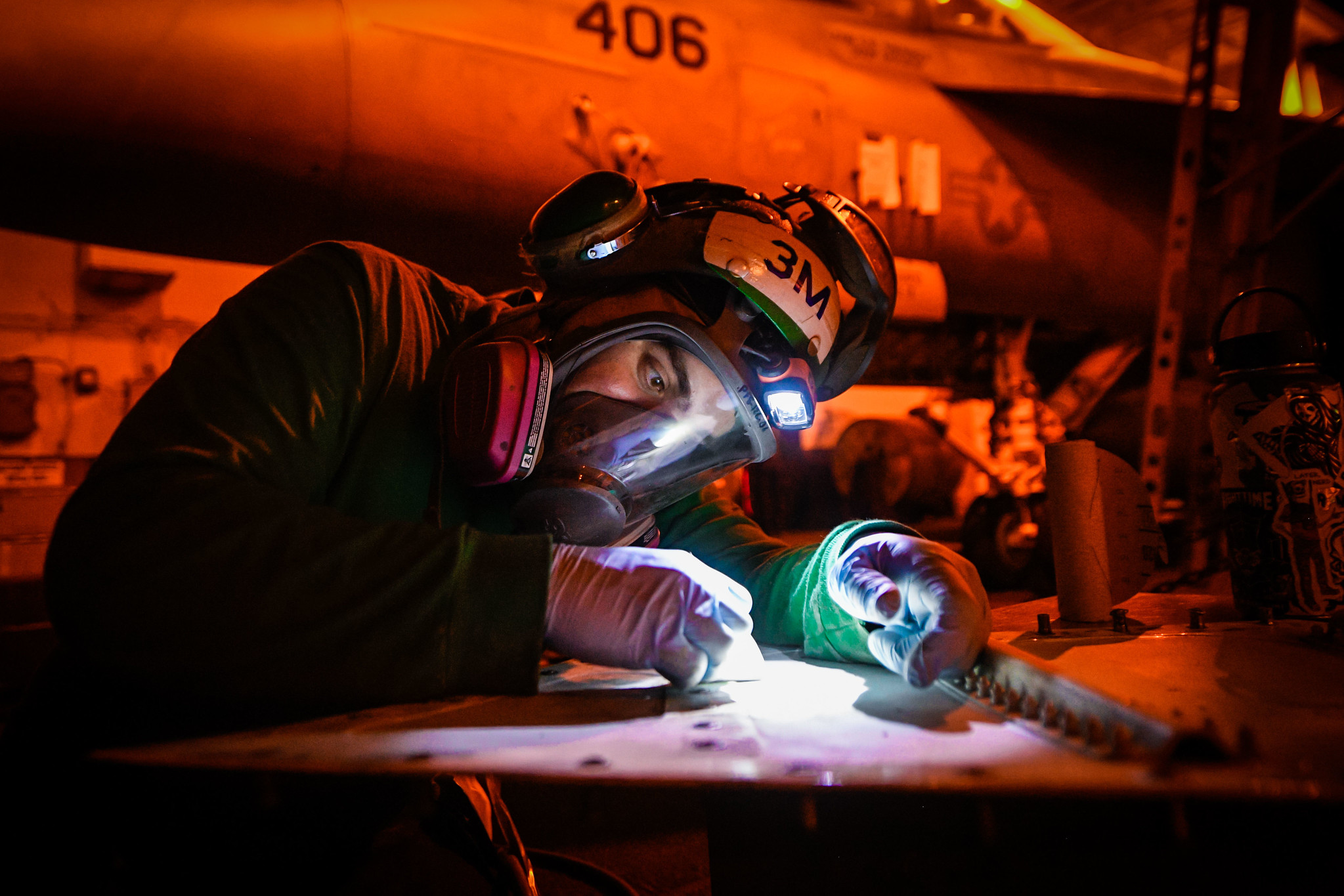Aviation Structural Mechanic 3rd Class James Murray removes corrosion from a panel on an F/A-18E Super Hornet on March 2, 2020, in the hangar bay of the aircraft carrier Theodore Roosevelt (CVN 71) in the Pacific Ocean. (Mass Communication Specialist Seaman Olympia O. McCoy/Navy(