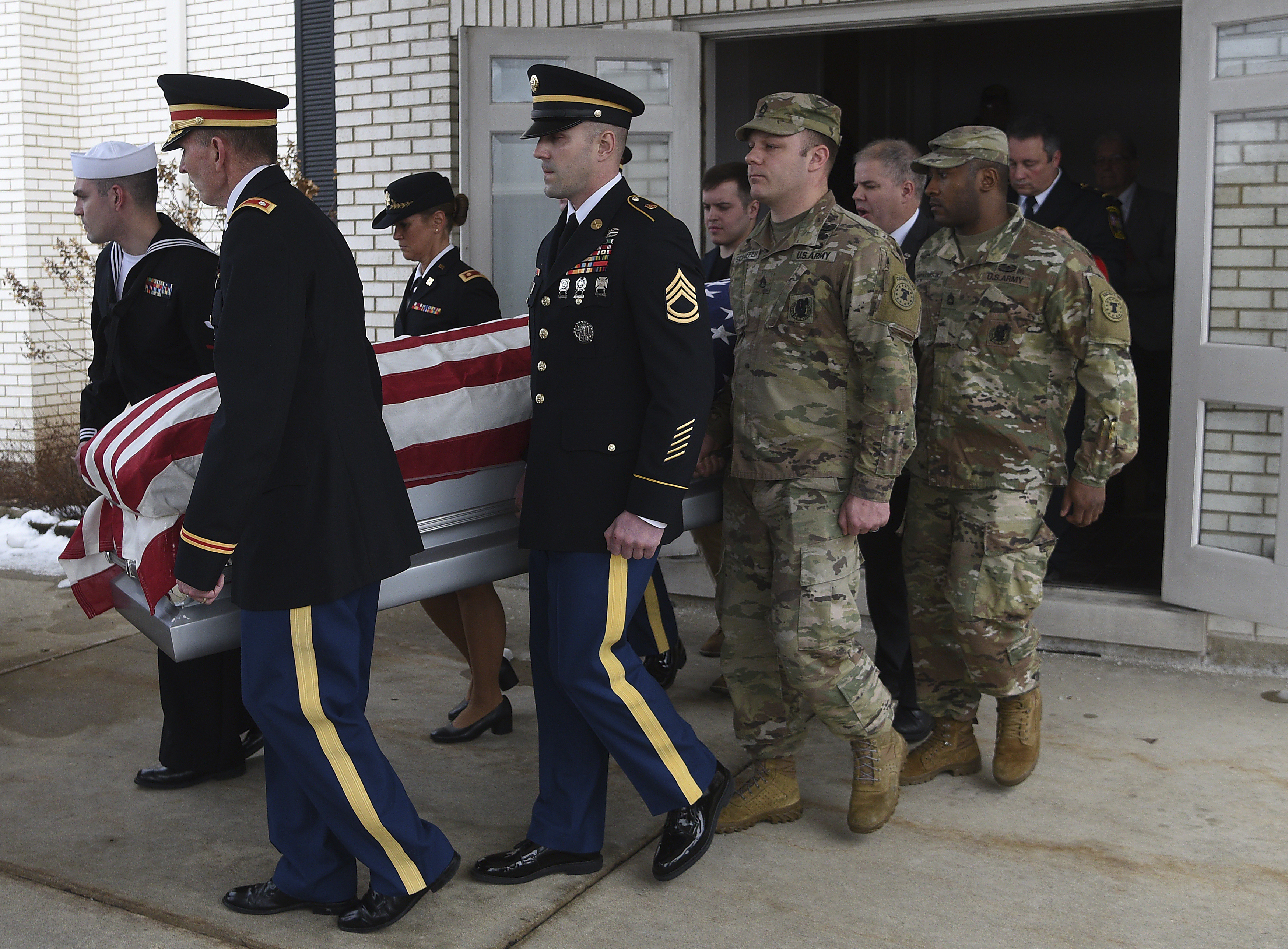 Active duty military members who were in attendance carry the casket. (AP)