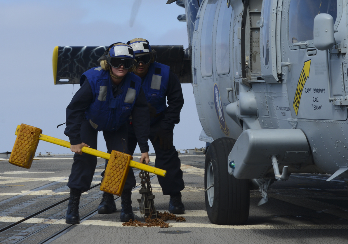 Boatswain's Mate 3rd Class Dylan Poston, right, waits next to an MH-60S Knight Hawk aboard the destroyer Stockdale in 2015. Poston is charged with the murder of another San Diego sailor, Anderson Lopes. (MC3 Susan C. Damman/Navy)