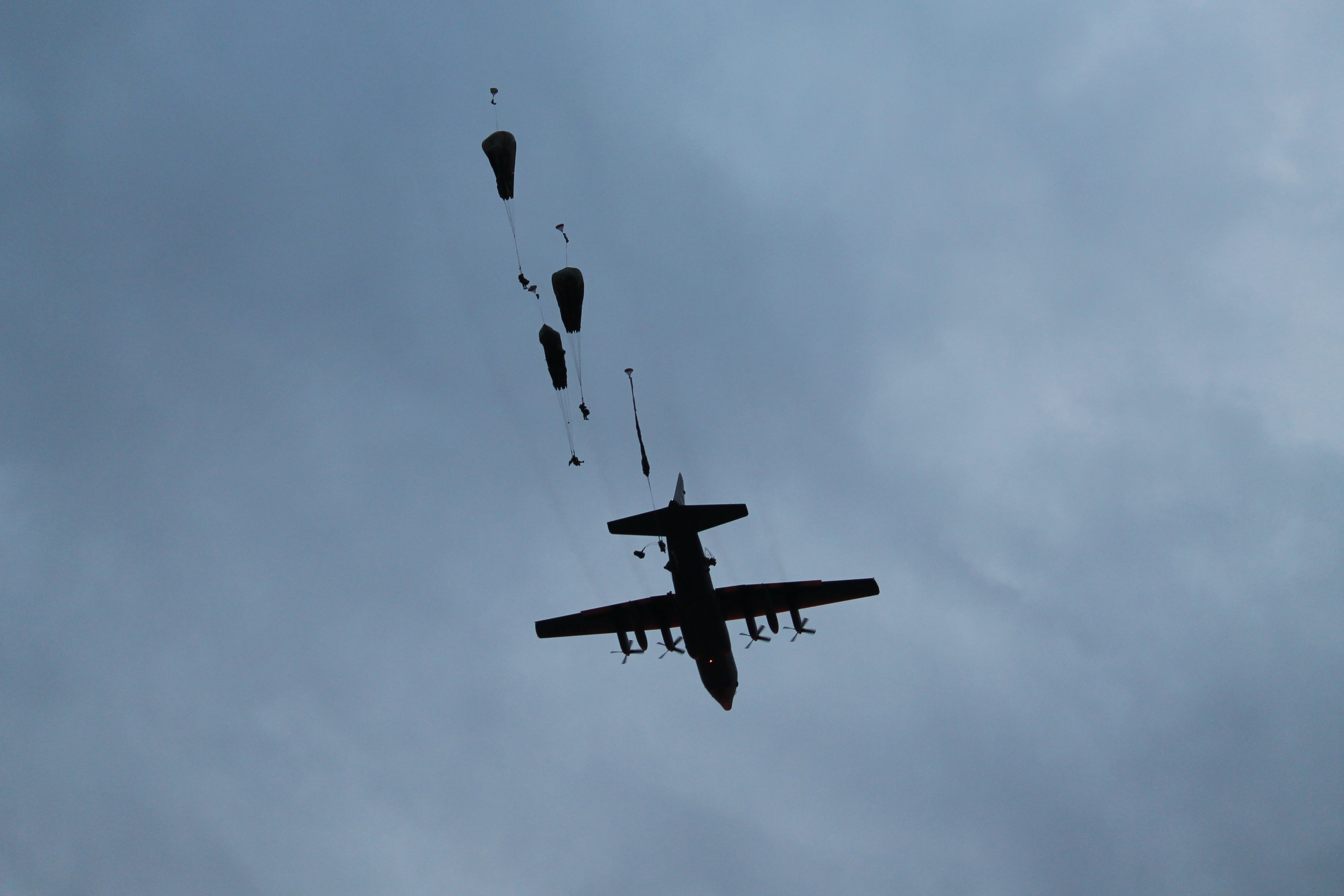 A C-130 flies overhead as paratroopers begin to jump out. The 13 aircraft used in Swift Response deposited hundreds of paratroopers at Bezmer over the course of roughly an hour. An estimated 1,000 paratroopers participated in Swift Response. (Jen Judson/Staff)