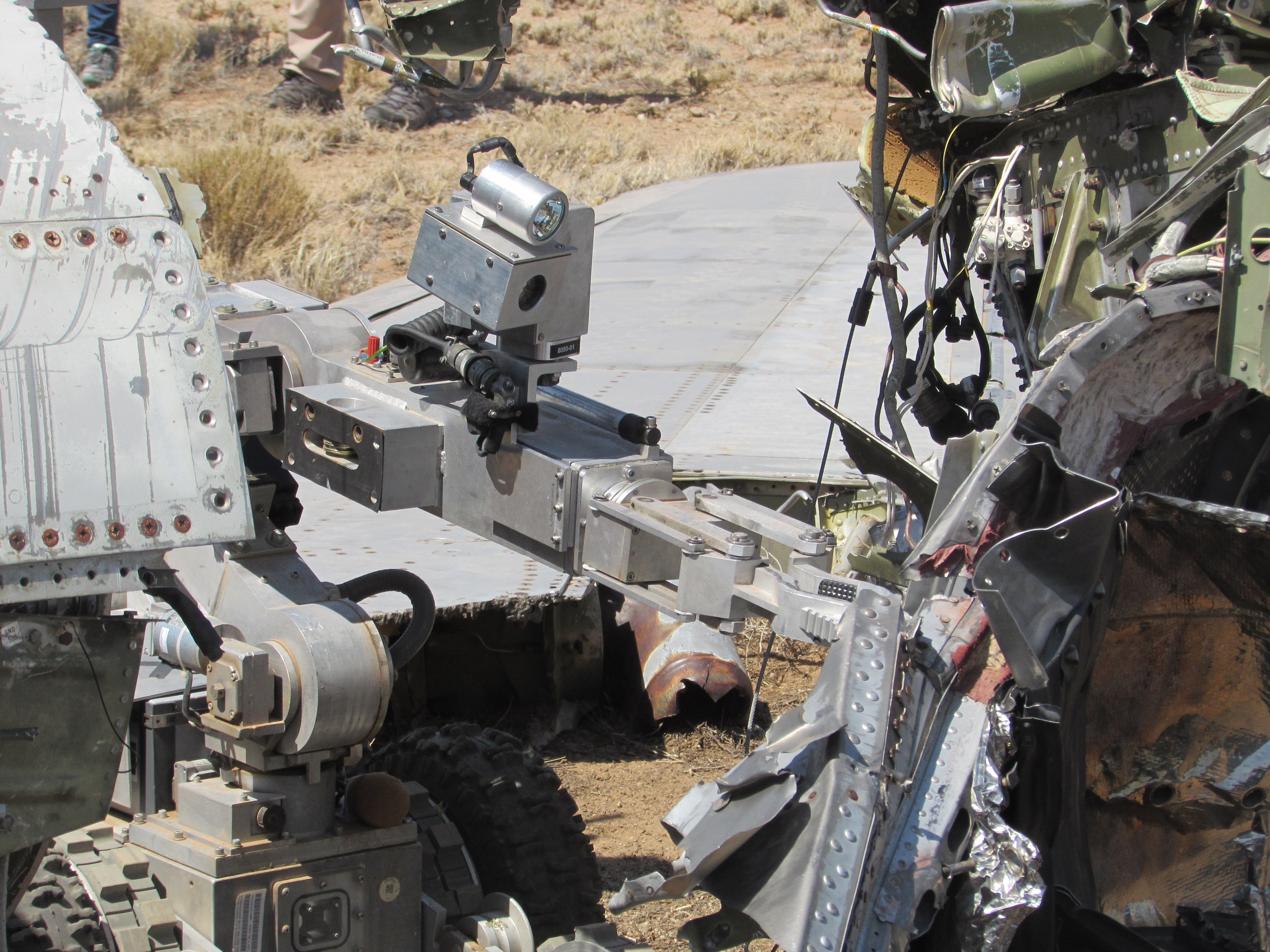 Driving between the two halves of the wrecked plane, the robot pokes around for clues about suspected mock explosives. (Kelsey D. Atherton)