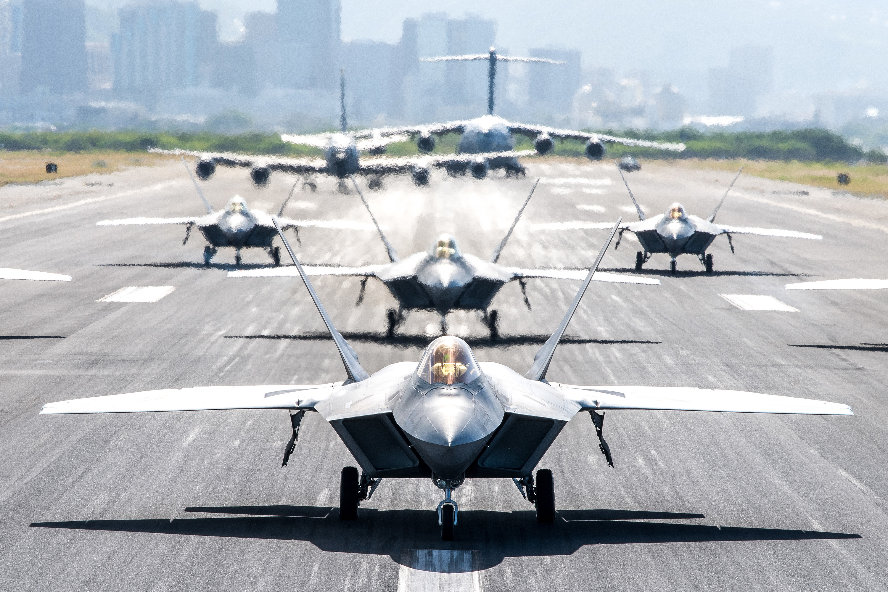 F-22 Raptors, a KC-135 Stratotanker and a C-17 Globemaster III taxi on the runway during a routine training schedule April 21, 2020, at Honolulu International Airport, Hawaii. (Senior Airman John Linzmeier/Air National Guard)
