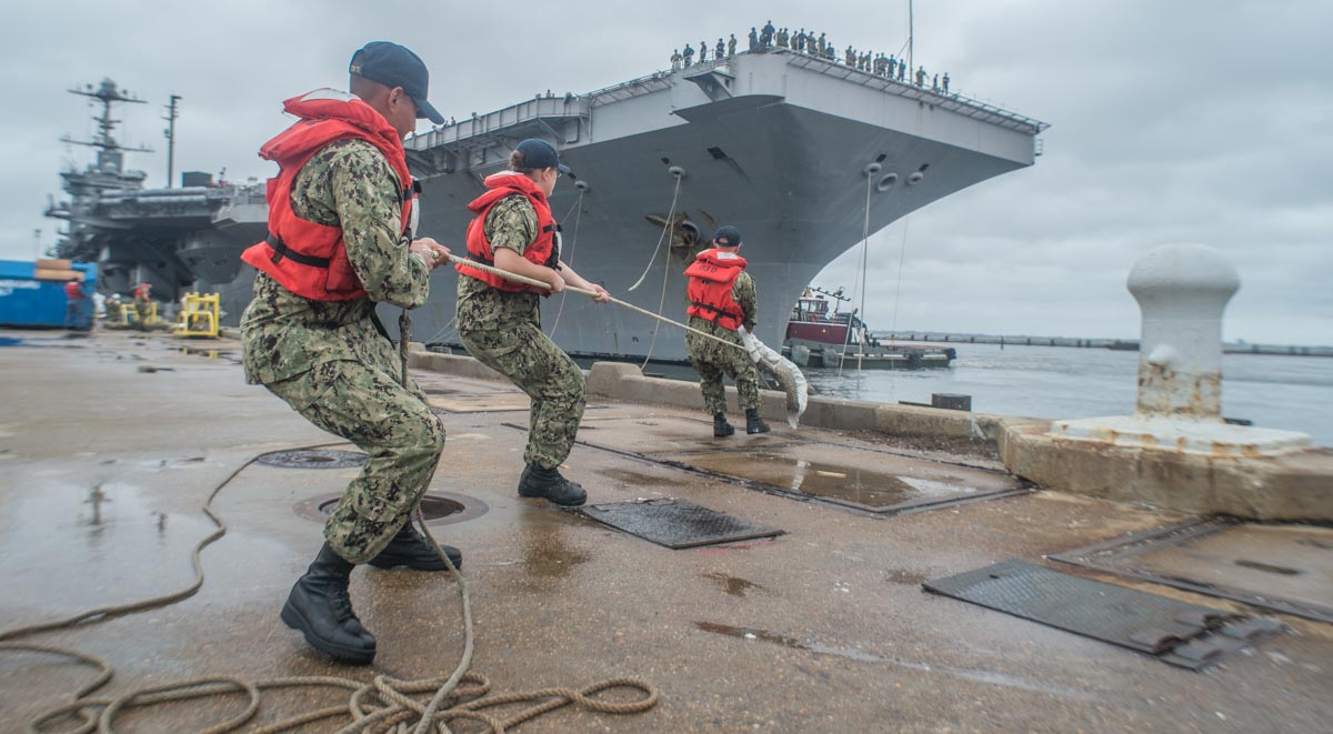 Naval Station, Norfolk, Va. (July 21, 2018) Sailors from the nearby aircraft carrier Abraham Lincoln pull on lines from the aircraft carrier Harry S. Truman who arrived back at Norfolk Naval Station, July 21. photo by Mark D. Faram/staff)