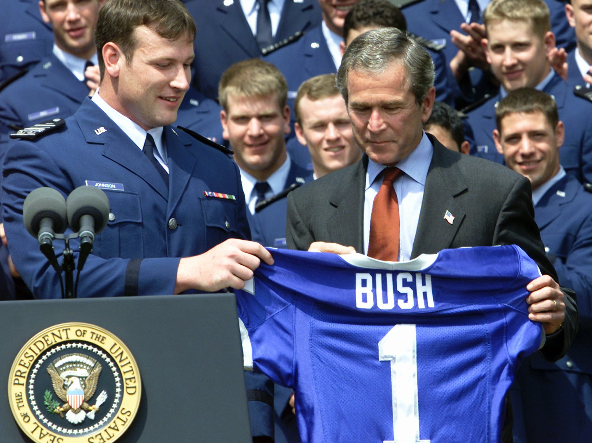 President Bush receives an Air Force football jersey from cadet Zack Johnson of Junction City, Ore., during the presentation of the Commander-in-Chief's Trophy to the the U.S. Air Force Academy football team in the Rose Garden, at the White House Friday, May 17, 2002. (AP Photo/Rick Bowmer)