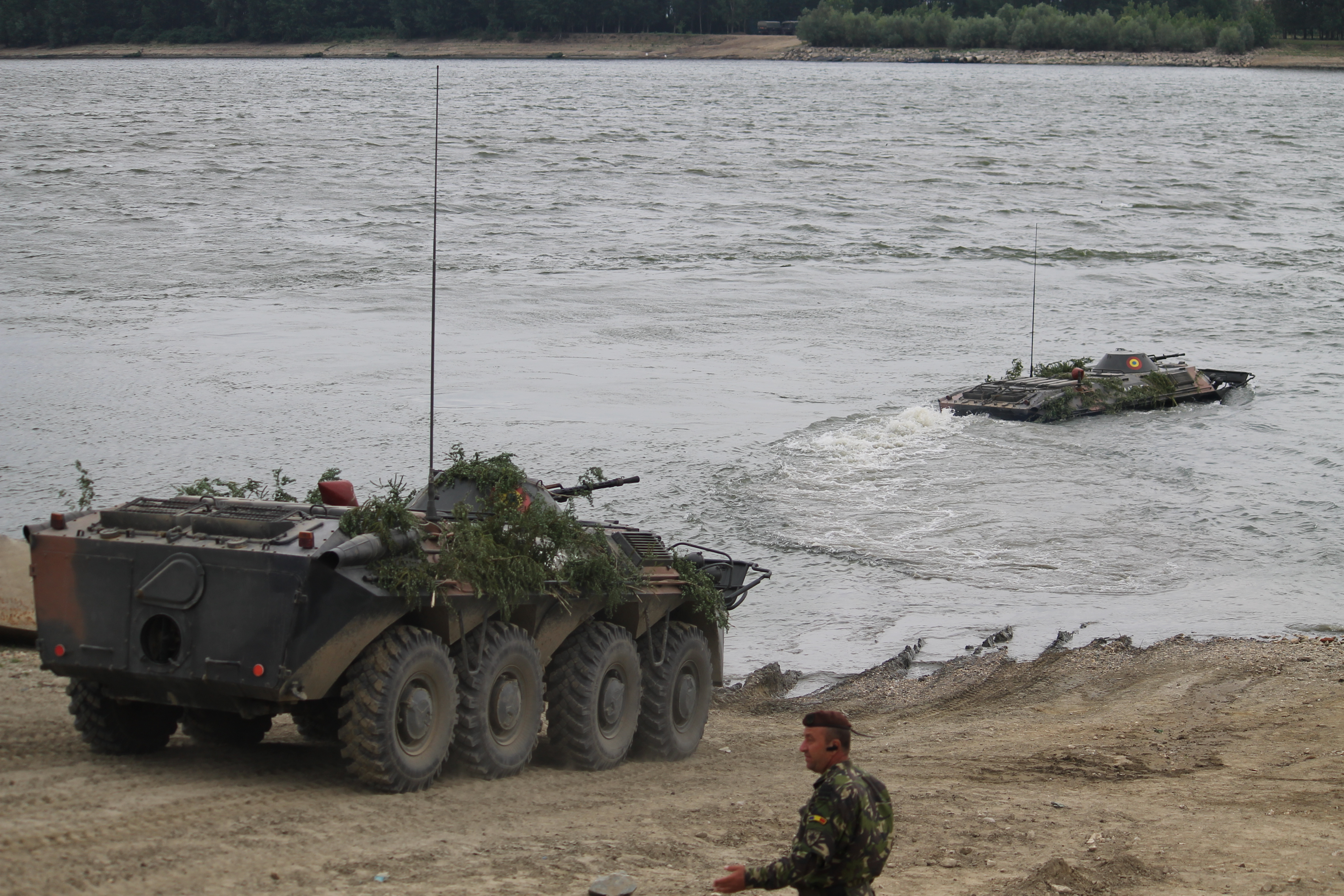 Romanian BTR armored vehicles move into the river as troops fire their guns. Using armored vehicles to swim the Danube is a move the Soviets developed in the Warsaw Pact and practiced regularly. The Romanians brought back the capability during the exercise using an entire company of BTRs. (Jen Judson/Staff)