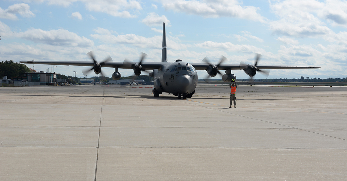 A 157th Air Refueling Wing Airman guides a Lockheed C-130 Hercules as it taxis on the flightline on Oct. 15, 2017, at Pease Air National Guard Base, N.H. (Staff Sgt. Kayla Rorick/Air National Guard)