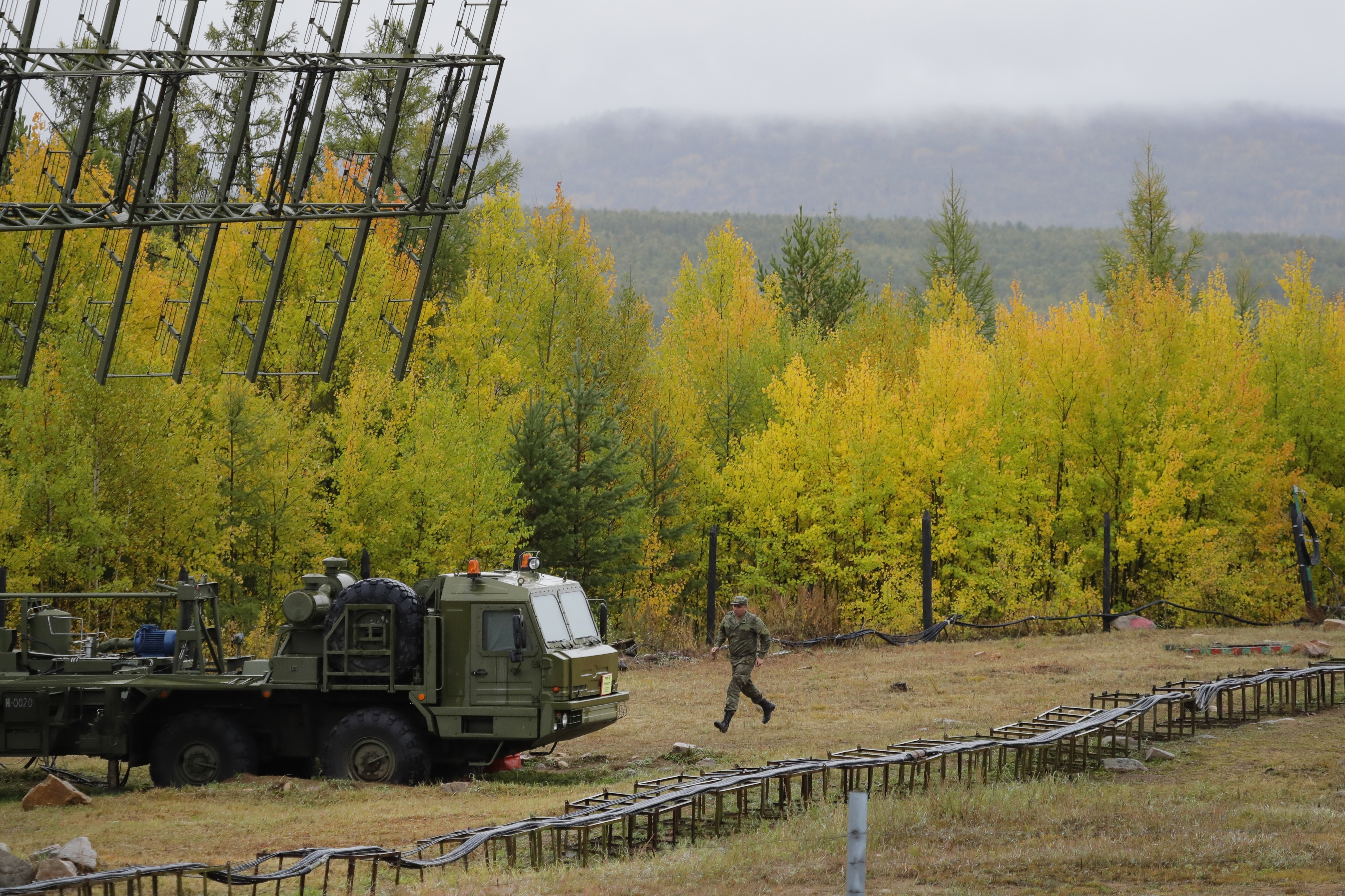 A Russian soldier runs towards a Nebo-M radar deployed by a forest, during a military exercises on training ground