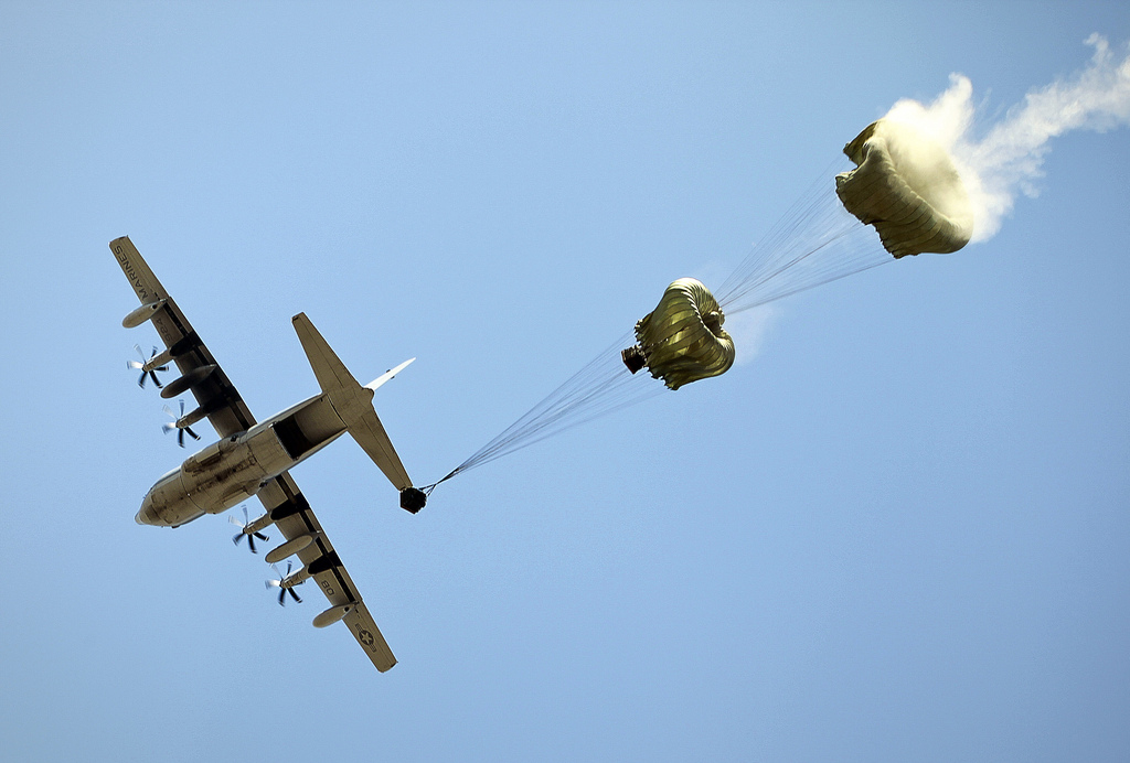 A C-130 transport aircraft airdrops container delivery systems with water cargo here Sept. 9, 2011. Marines conducted a live air delivery in support of a humanitarian assistance operation exercise. (Marine Corps)