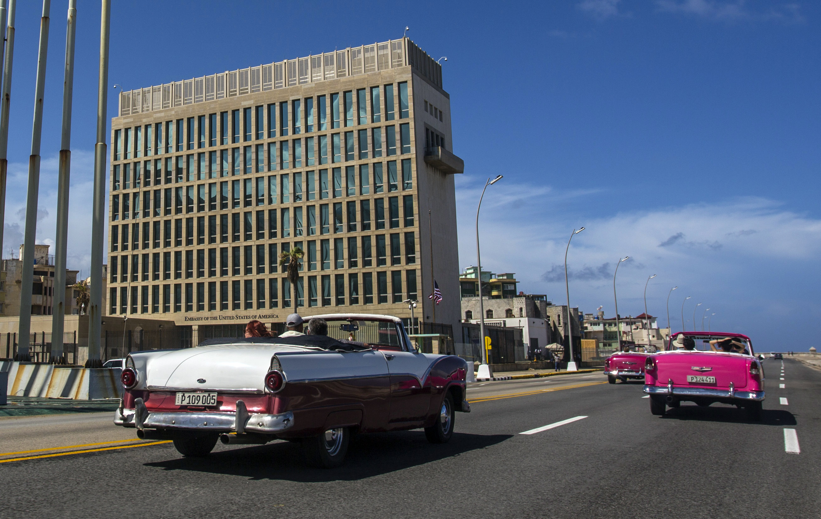In this Oct. 3, 2017 photo, tourists ride classic convertible cars on the Malecon beside the United States Embassy in Havana, Cuba. (AP Photo/Desmond Boylan)