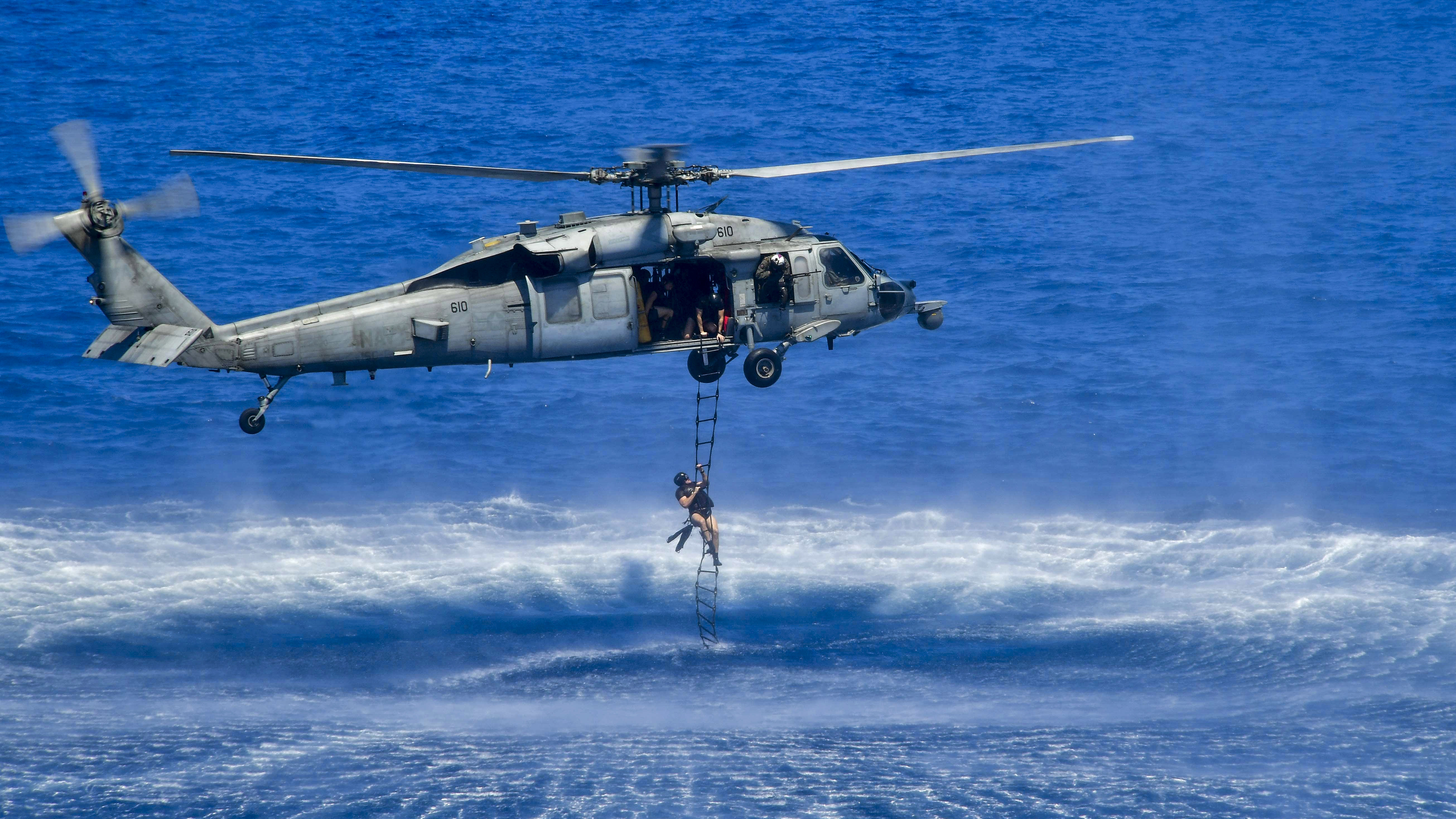 A Sailor, assigned to Explosive Ordnance Disposal Mobile Unit (EODMU) 1, climbs a rescue ladder attached to an MH-60S Sea Hawk, assigned to the Indians of Helicopter Sea Combat Squadron (HSC) 6, during a training exercise. EODMU 1 is embarked aboard the aircraft carrier USS Theodore Roosevelt (CVN 71), currently underway for a regularly scheduled deployment in the U.S. 7th Fleet area of operations in support of maritime security operations and theater security cooperation efforts. (MC3 Anthony J. Rivera/Navy)