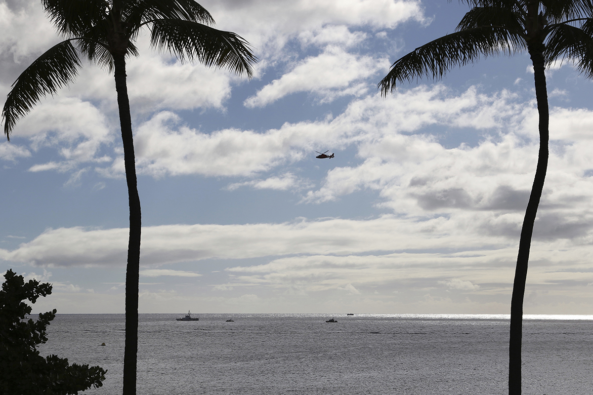 A U.S. Coast Guard helicopter flies over rescue boats at the scene of plane crash off Honolulu, Wednesday, Dec. 12, 2018. Federal Aviation Administration spokesman Ian Gregor said a Hawker Hunter jet went down in the ocean around 2:25 p.m. after taking off from Honolulu's airport. A civilian contractor for the Hawaii Air National Guard who was participating in a military exercise survived after his plane crashed off the coast of Honolulu, authorities said Wednesday. (Caleb Jones/AP)