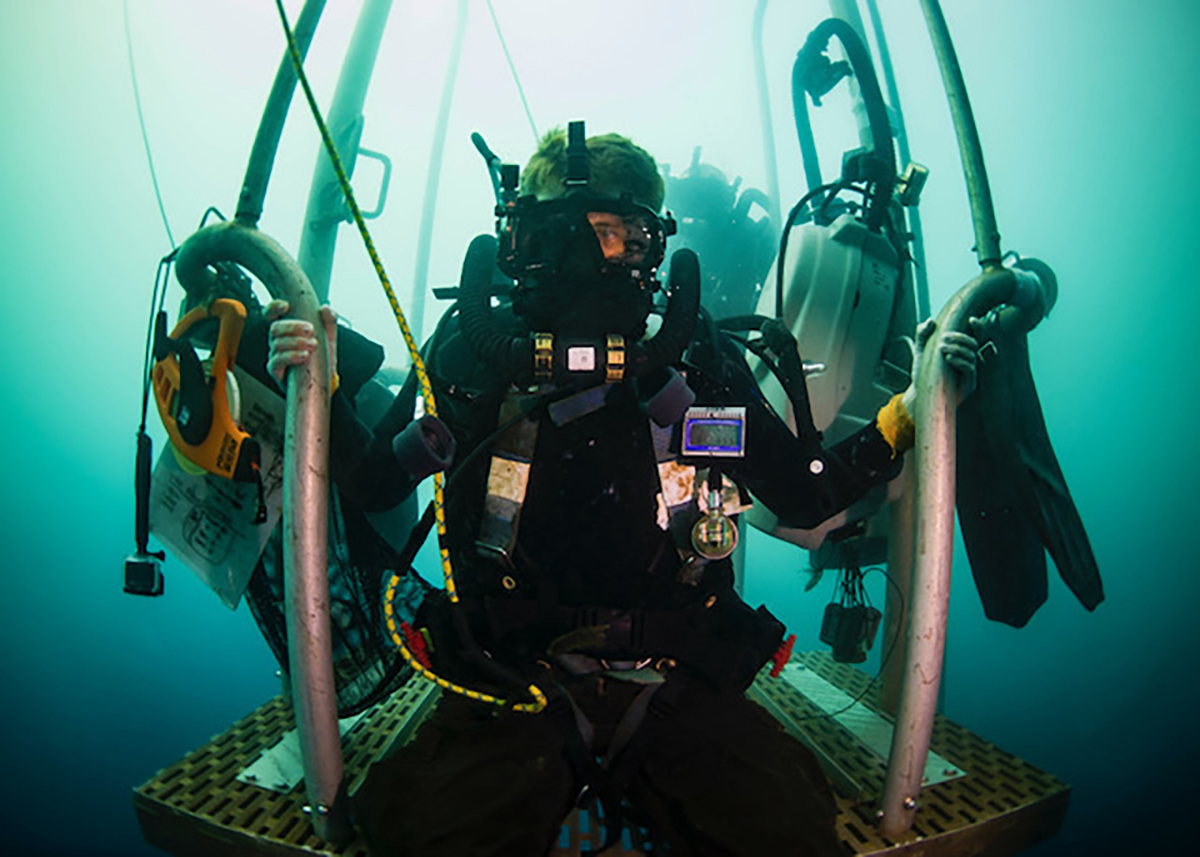 Navy Diver 1st Class James Mostek waits on a diving stage during a two-hour decompression stop after diving to 240 feet on Dec. 7, 2018. The sailor completed a Defense POW/MIA Accounting Agency underwater recovery mission searching for personnel who went missing during WWII in Papua New Guinea. (MC1 Tyler Thompson/Navy)