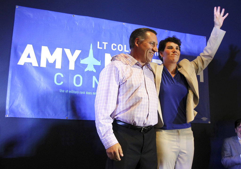 Amy McGrath, right, with her husband, Erik Henderson, waves to supporters after being elected as the Democratic candidate for Kentucky's 6th Congressional District, Tuesday, May 22, 2018, in Richmond, Ky. (James Crisp/AP)