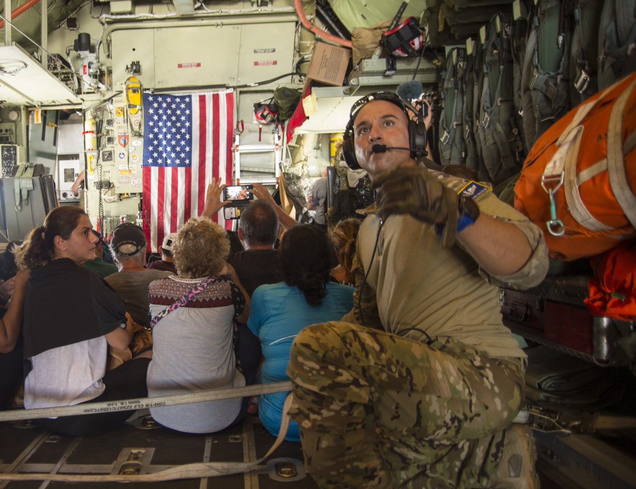 Master Sgt. James Brucculeri, loadmaster with the 103rd Rescue Squadron, ushers evacuees onto a HC-130 on St. Maarten headed to San Juan, Puerto Rico, on Sept. 10, 2017. (Staff Sgt. Erin Mills/Air Force)