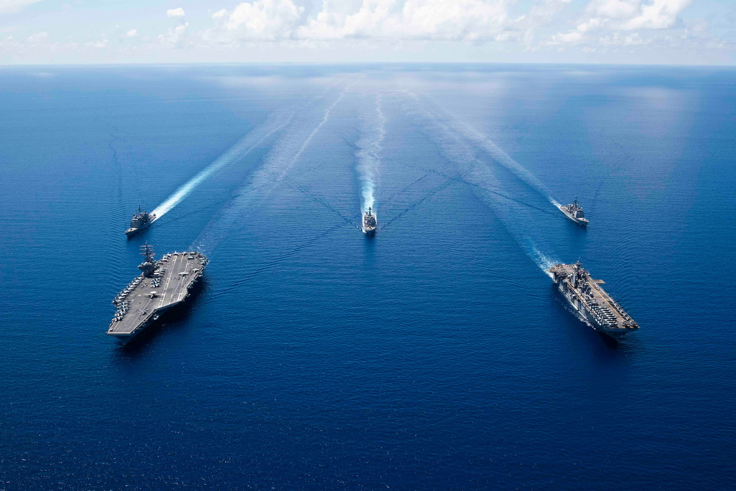 The aircraft carrier USS Ronald Reagan (CVN 76), left, and the amphibious assault ship USS Boxer (LHD 6) and ships from the Ronald Reagan Carrier Strike Group and the Boxer Amphibious Ready Group are underway in formation Oct. 6, 2019, in the South China Sea. (Mass Communication Specialist 2nd Class Erwin Jacob V. Miciano/Navy)