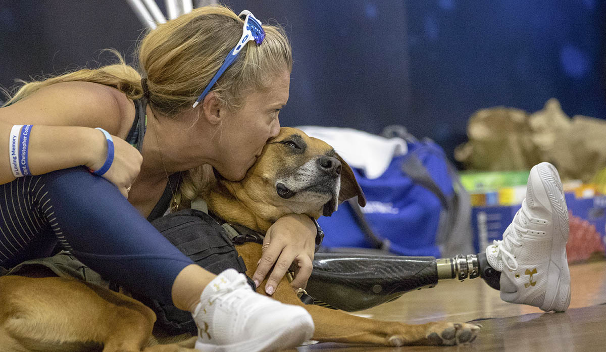 Retired Senior Airman Heather Carter takes a break with service dog Rocky after competing in sitting volleyball at the Department of Defense Warrior Games 2018. Warrior Games is a Paralympic style competition where wounded warriors compete in 11 different adaptive sporting events. Competition this year started 1 June and runs through 9 June. (Master Sgt. David Long/Air Force)