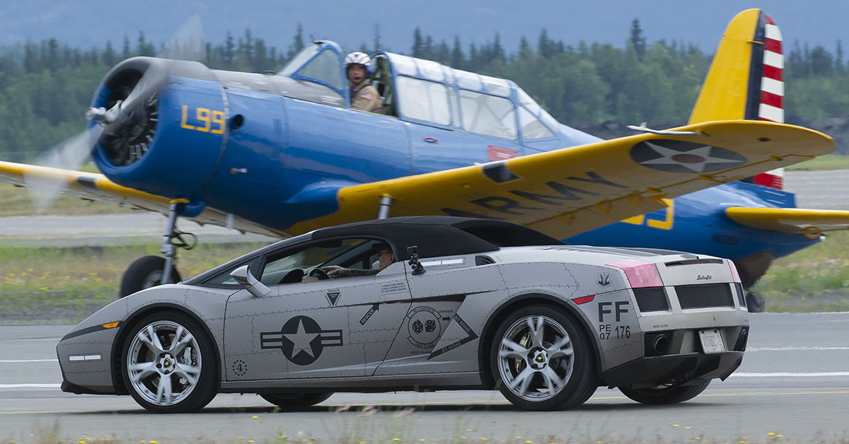 A Lamborghini accelerates down the runway past a BT-13 waiting to take off during the Arctic Thunder Open House, June 30, 2018. This biennial event hosted by Joint Base Elmendorf-Richardson, Alaska, is one of the largest in the state and one of the premier aerial demonstrations in the world. (Justin Connaher/Air Force)