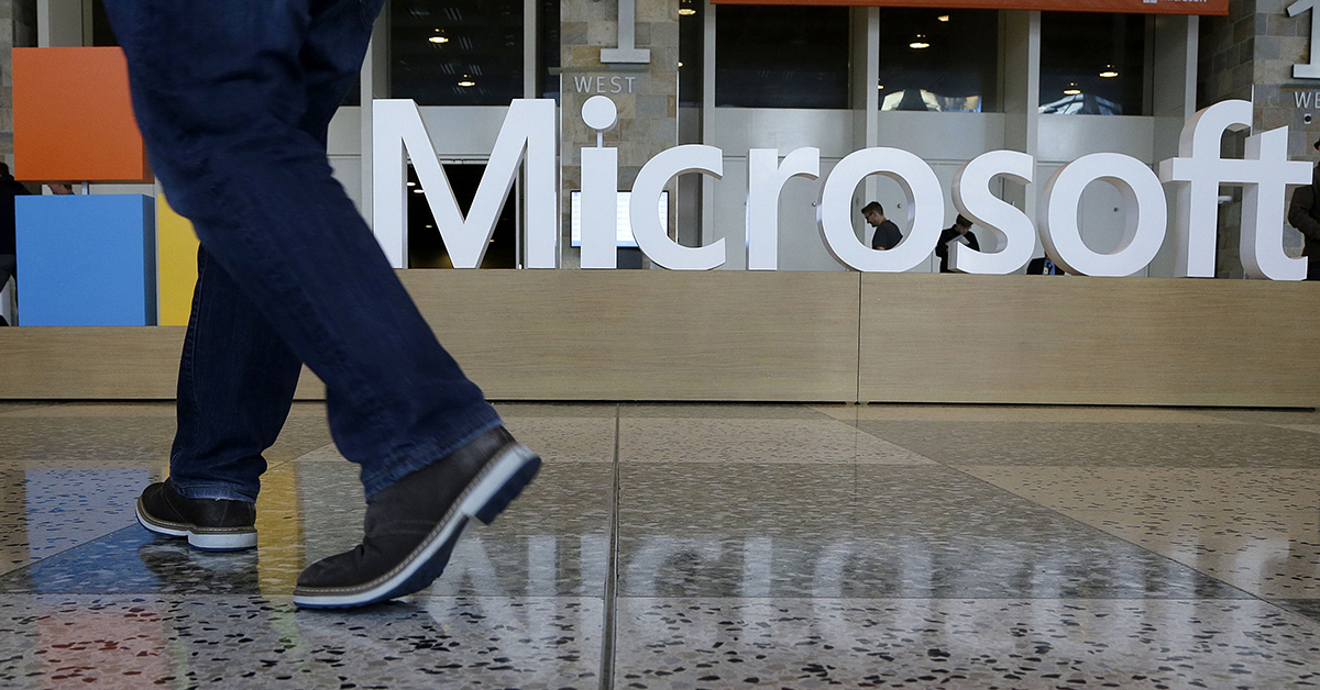 In this April 28, 2015, file photo, a man walks past a Microsoft sign set up for the Microsoft BUILD conference at Moscone Center in San Francisco. Microsoft has uncovered new hacking attempts by Russia targeting U.S. political groups ahead of the midterm elections. The company said Tuesday, Aug. 21, 2018, that a group tied to the Russian government created fake websites that appeared to spoof two American conservative organizations: the Hudson Institute and the International Republican Institute. Three other fake sites were designed to look as if they belonged to the U.S. Senate. (Jeff Chiu/AP)